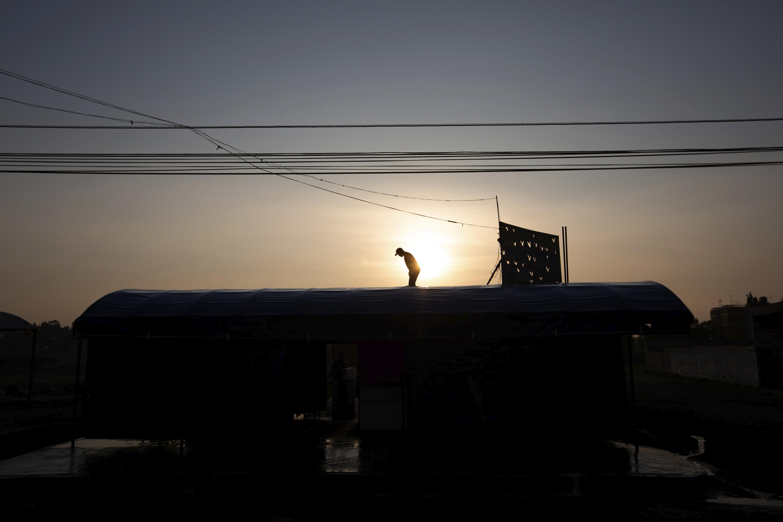 Un hombre lava con agua y jabón el techo de su restaurante como medida de precaución en medio de la propagación del nuevo coronavirus en San Andrés Mixquic, México, el lunes 30 de marzo de 2020.