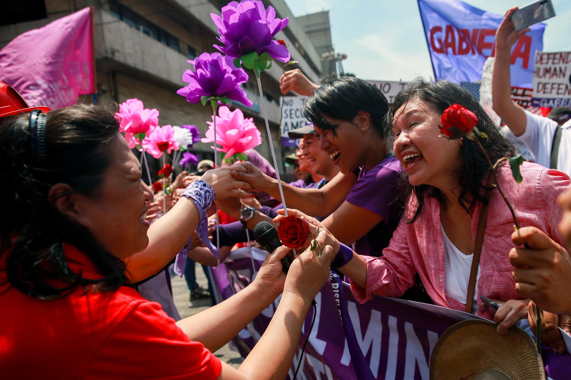 Mujeres intercambian flores durante la marcha en Manila, Filipinas (REUTERS/Eloisa Lopez)