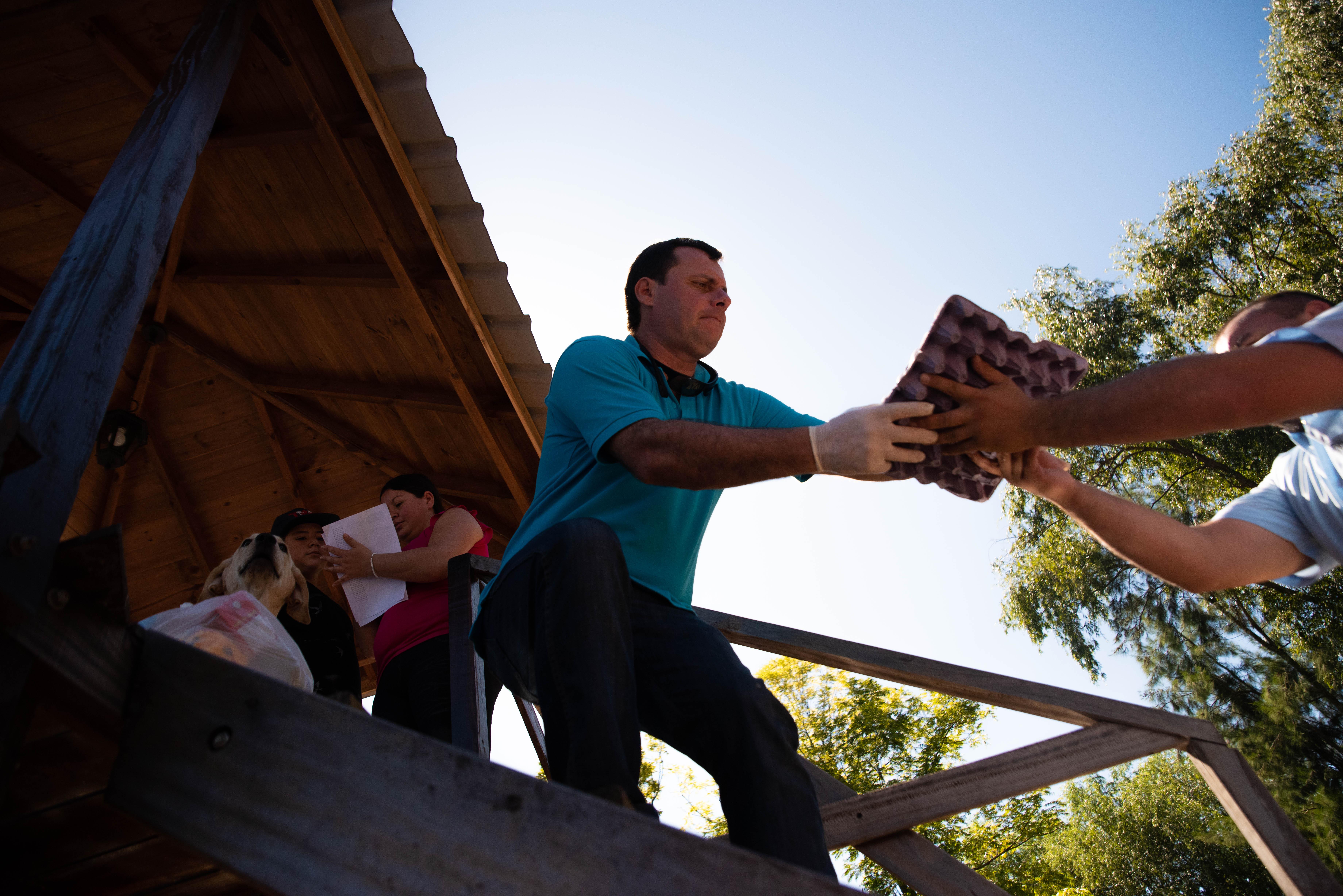 Diego, uno de los docentes que participó de la entrega de kits, descarga alimentos frente a la casa de uno de sus alumnos. (Foto: Franco Fafasuli)