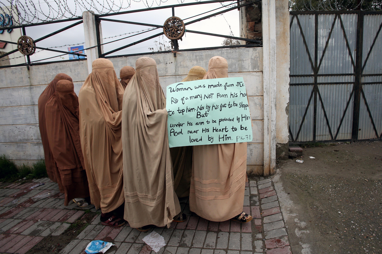 Mujeres simpatizantes del partido político y religioso Jamiat Ulema-e-Islam-Fazal (JUI-F) vestidas con burkas, sostienen una pancarta para asistir a una Marcha de las Mujeres, en Peshawar, Pakistán (REUTERS / Khurram Parvez)