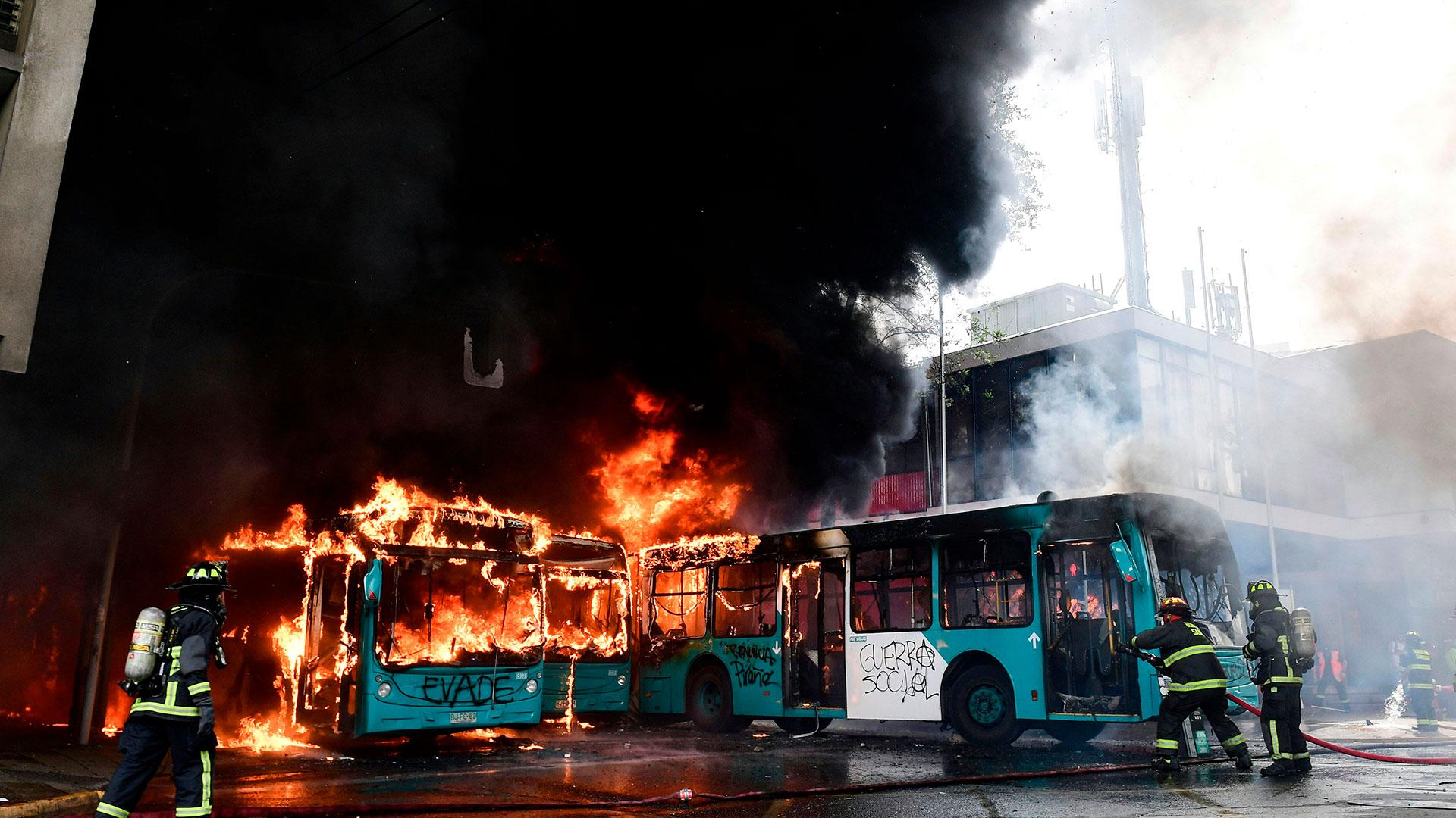 Los bomberos santiaguinos combaten las llamas dentro de los autobuses públicos.