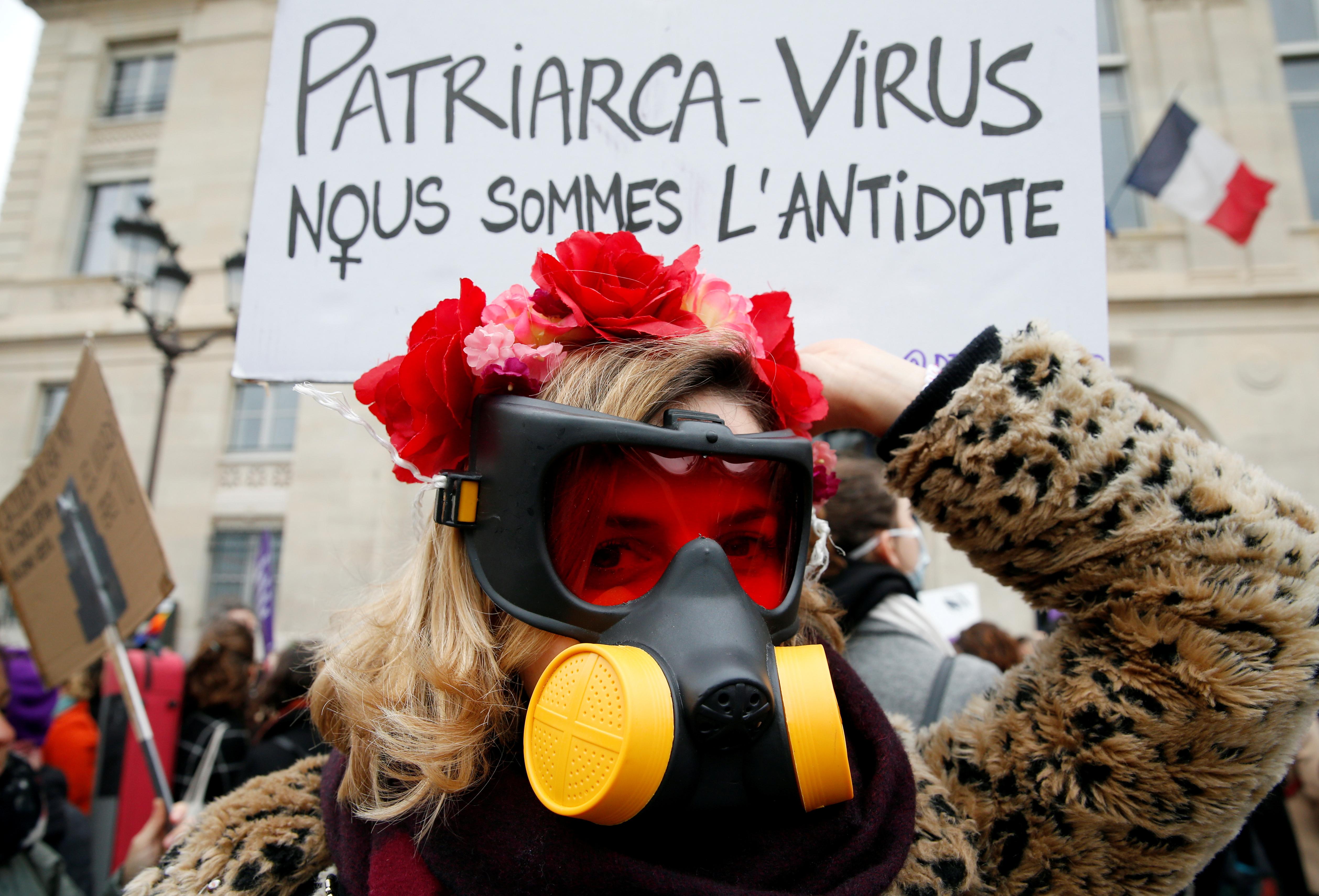 Una mujer con una máscara de gas asiste a una protesta exigiendo la igualdad en el Día Internacional de la Mujer en París, Francia, el 8 de marzo de 2020. La pancarta dice