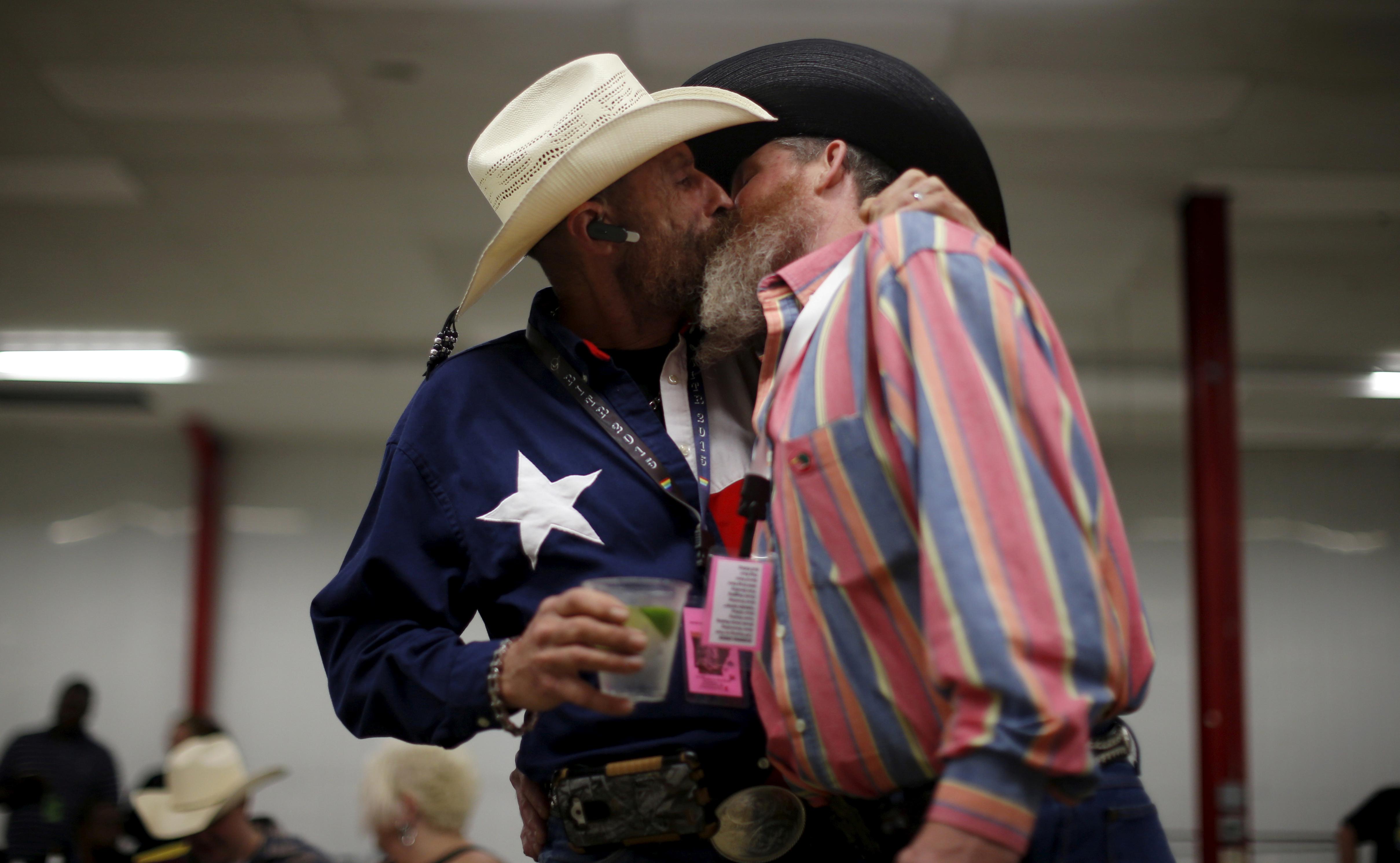 Gordon Satterly, de 61 años, de Michigan (izq.) besa a su esposo Richard Brand, de 53 años, de Texas, en la fiesta