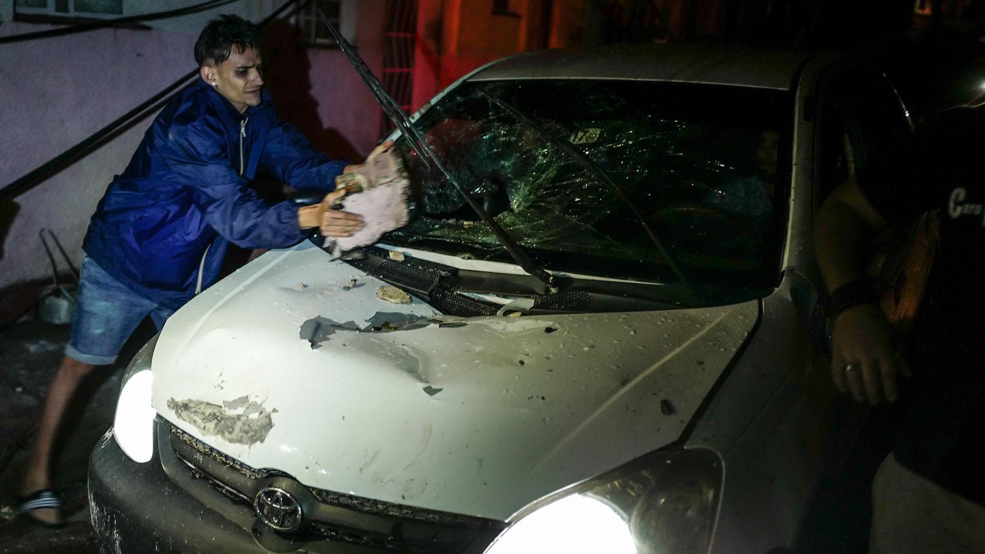 Un hombre trata de limpiar un automóvil que quedó maltrecho por el fenómeno (AFP)