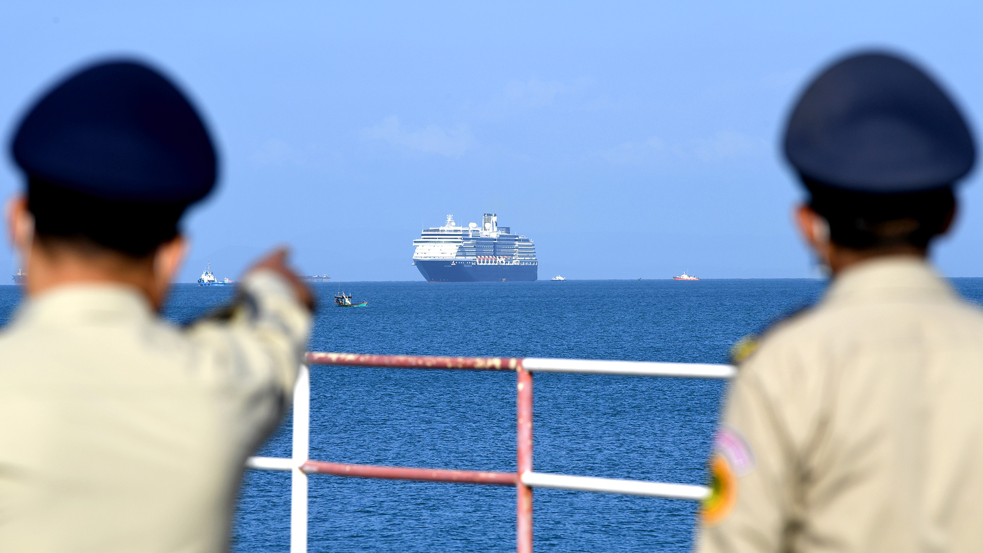 El crucero de Westerdam es visto por policías camboyanos cuando se acerca al puerto de Sihanoukville, la costa sur de Camboya, el 13 de febrero de 2020, donde el barco recibió permiso para atracar después de que se le negó la entrada a otros puertos asiáticos debido a los temores del coronavirus (TANG CHHIN Sothy / AFP)