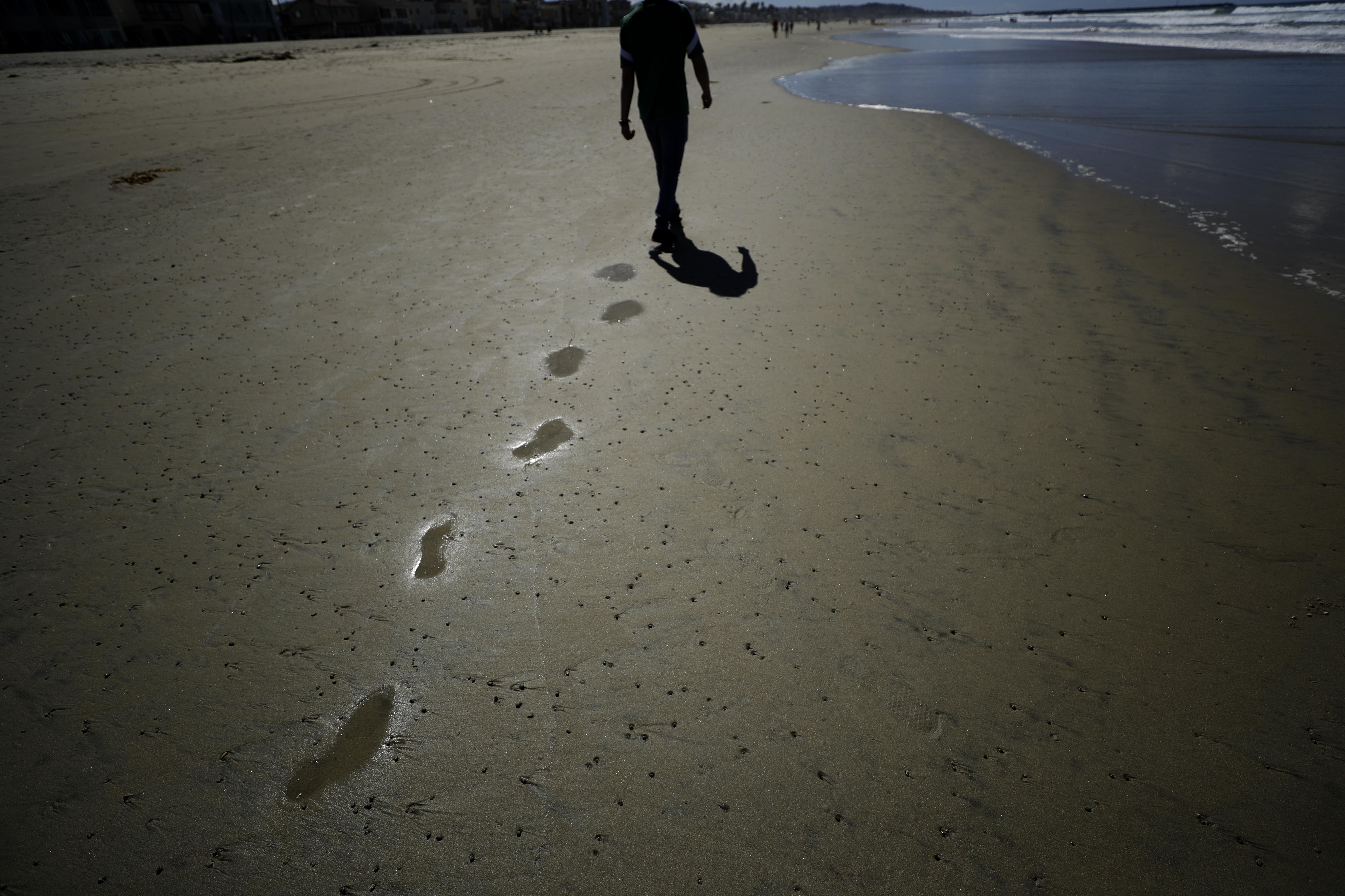El panorama es distinto en California, aunque con otras temperaturas. Un hombre camina por una playa vacía en San Diego (AP Photo/Gregory Bull)