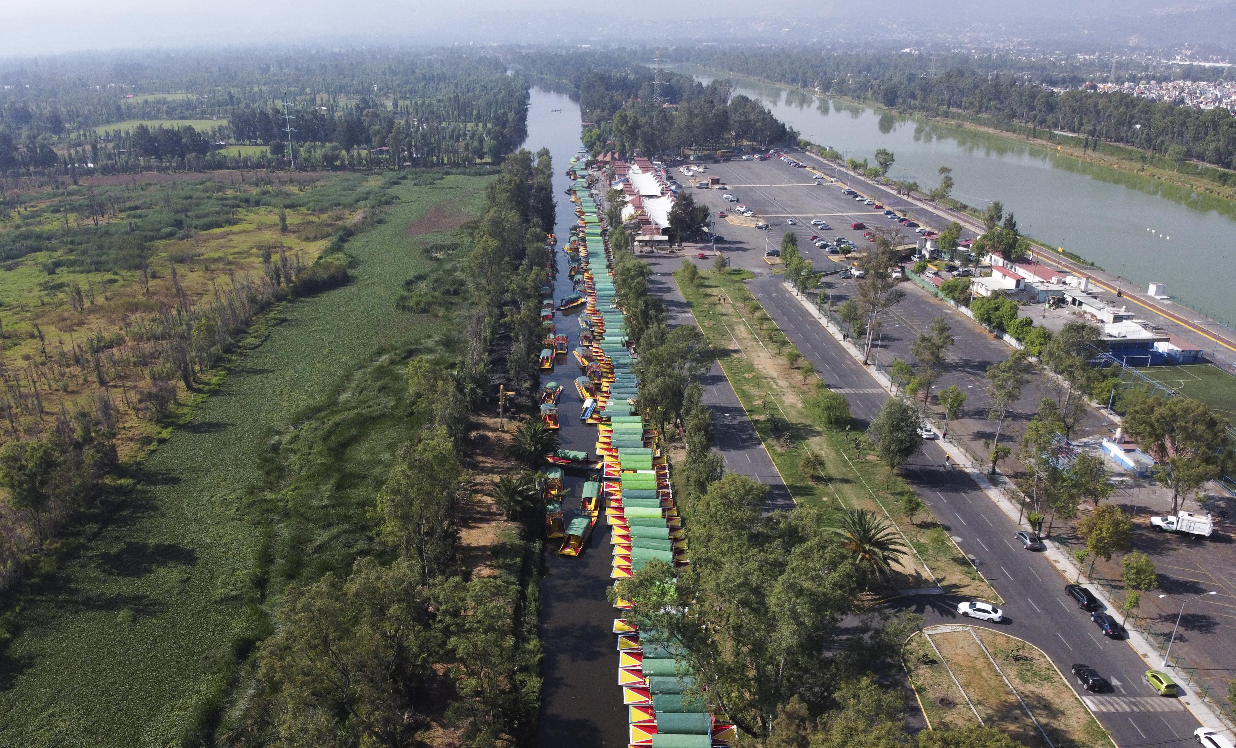 Una línea de trajineras, los botes de madera pintados populares entre los turistas que navegan por los canales en el distrito de Xochimilco de la Ciudad de México, esperan a los visitantes el domingo 22 de marzo de 2020.