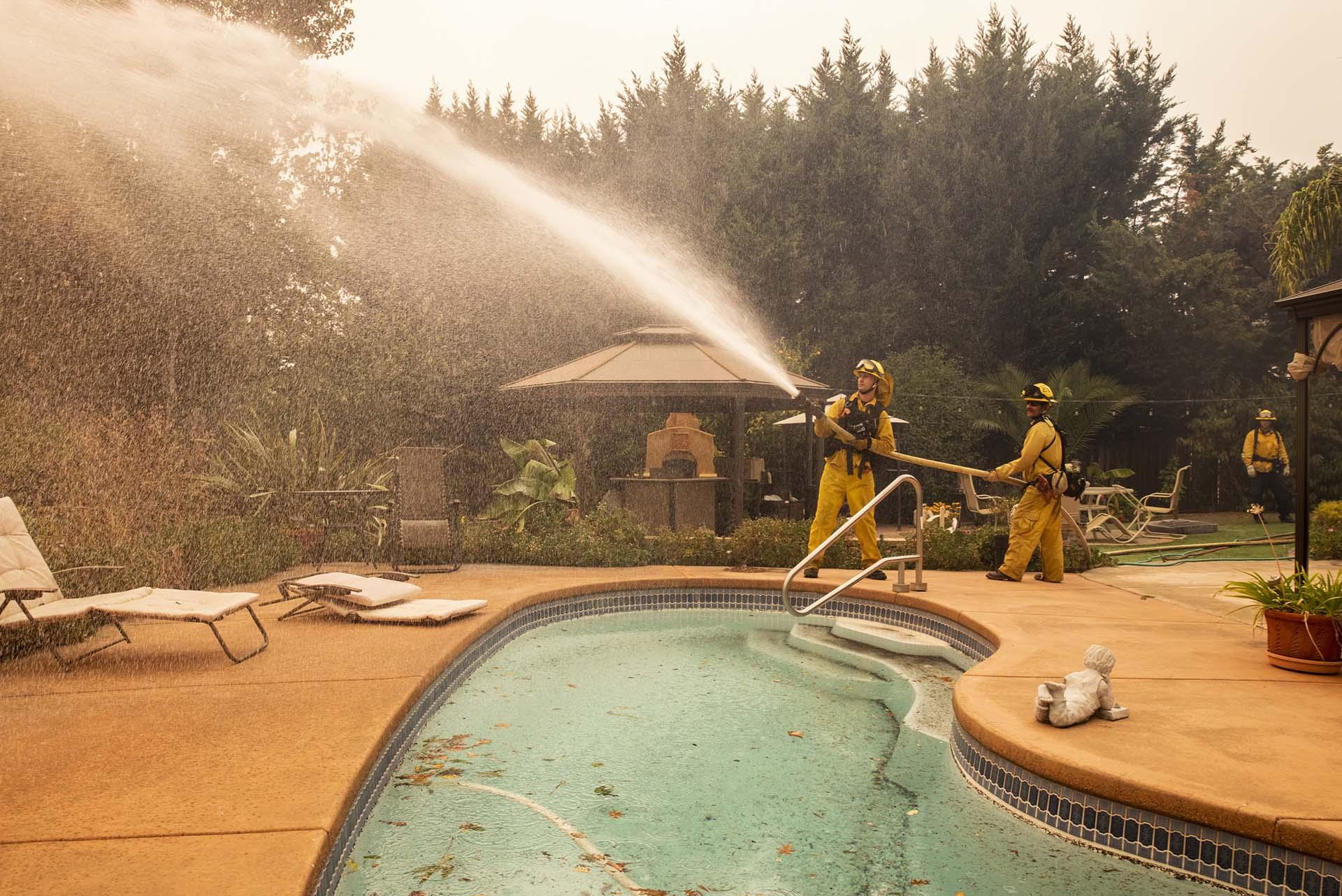 Los bomberos rocían agua en una fogata en una casa durante el incendio de Kincade en Vinecrest Road en Windsor, California, el domingo 27 de octubre de 2019