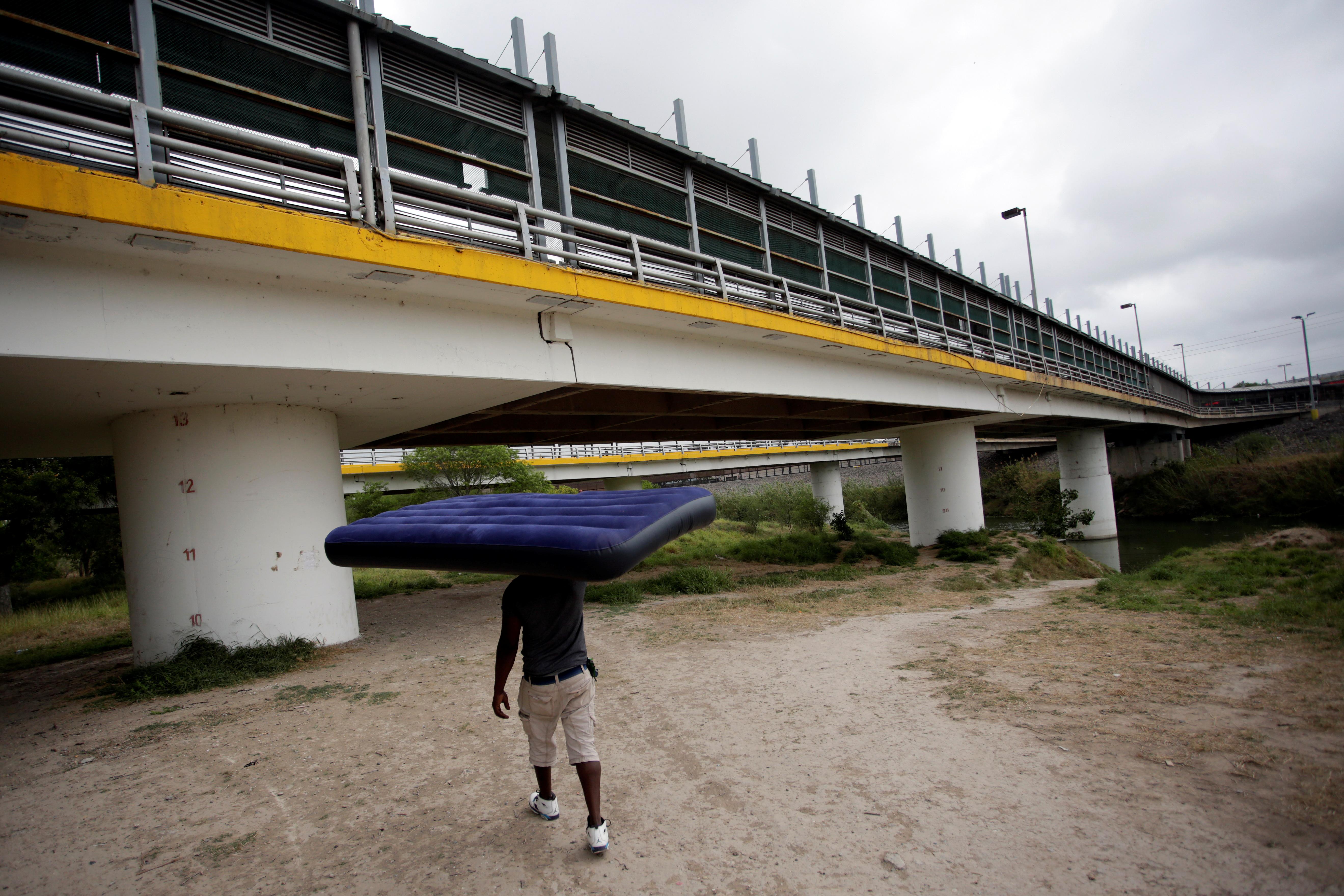 Un migrante de Haití, que busca asilo en los EE. UU., Lleva un colchón cerca del Puente Internacional Matamoros-Brownsville, cerca de un campamento de más de 2,000 migrantes, mientras las autoridades locales se preparan para responder al brote de la enfermedad por coronavirus (COVID-19) , en Matamoros, México 20 de marzo de 2020.