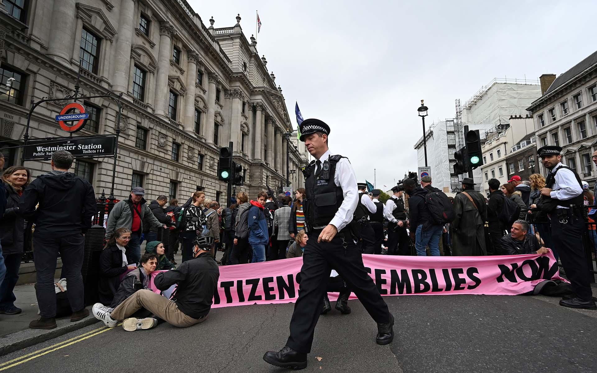 Oficiales de policía británicos hablan con activistas del cambio climático del grupo Extinction Rebellion, como lo demuestran mientras bloquean el cruce de las calles Whitehall y Parliament Square en el centro de Londres, el 7 de octubre de 2019. (Foto de Ben STANSALL / AFP)