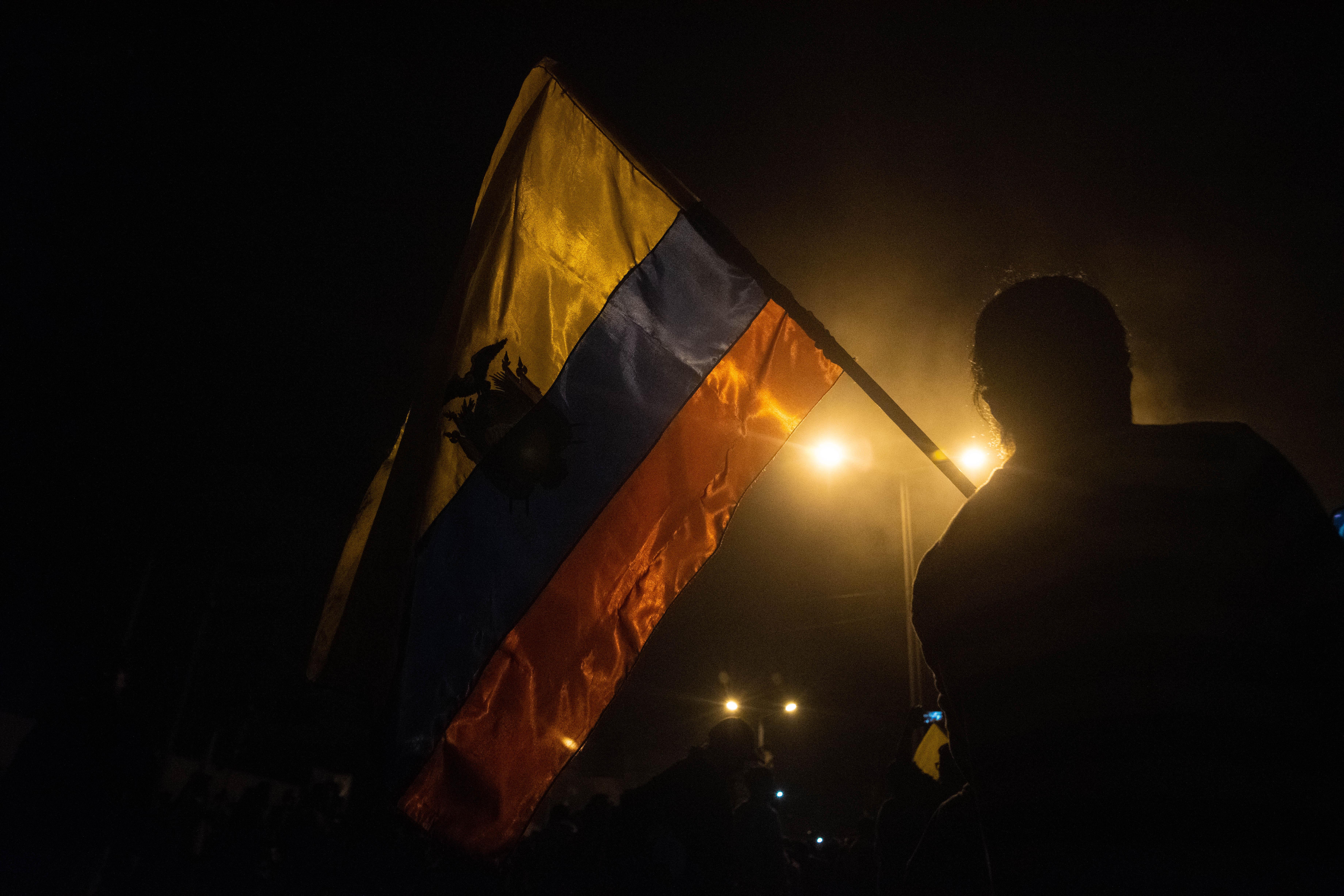 Un ciudadano festeja con la bandera ecuatoriana en alto durante las celebraciones que estallaron el domingo por la noche en la capital ecuatoriana.