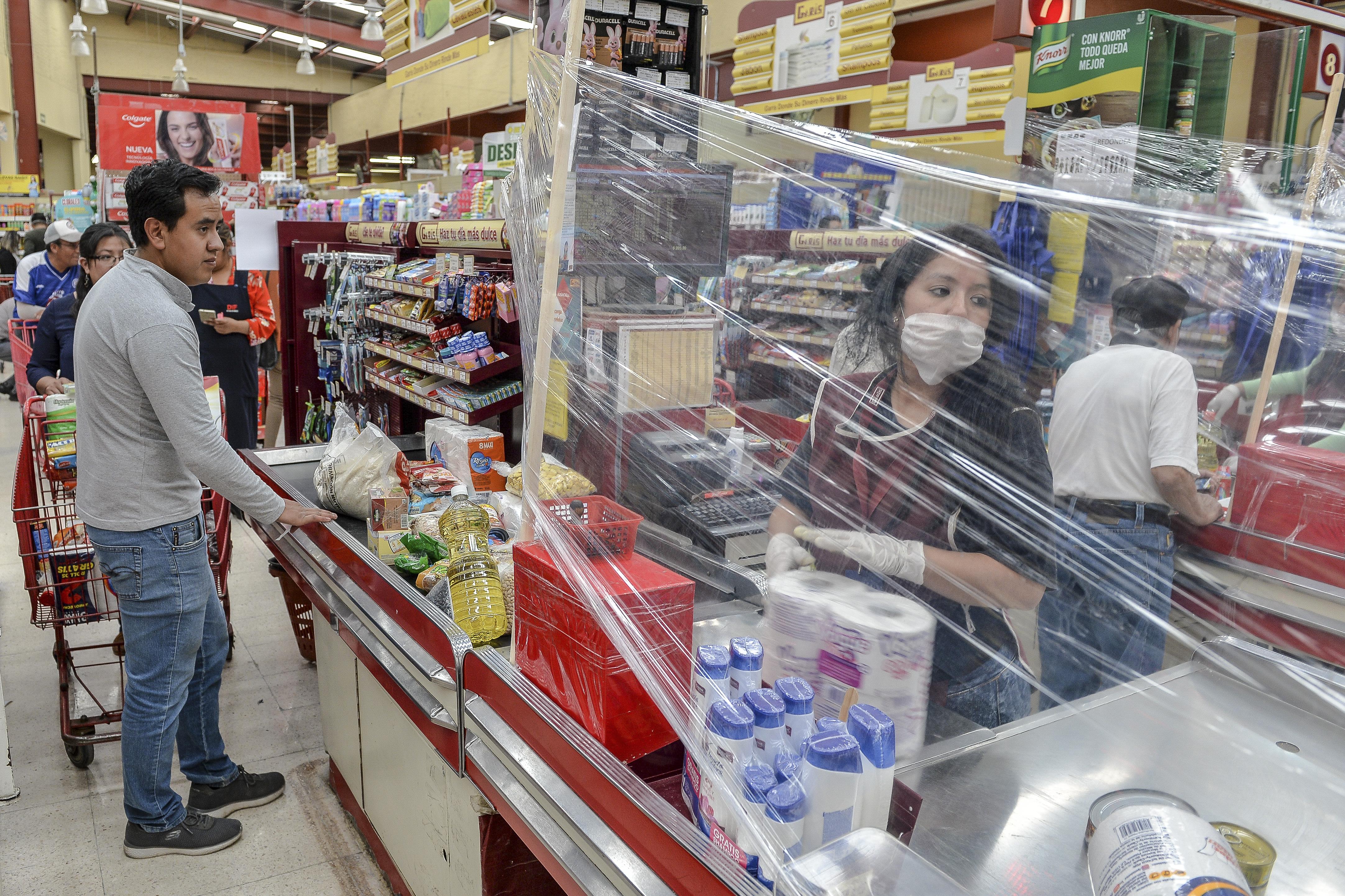 Un cajero detrás de una cortina de plástico improvisada como medida preventiva contra la propagación del nuevo coronavirus, COVID-19, en Toluca, Estado de México, México, el 27 de marzo de 2020.