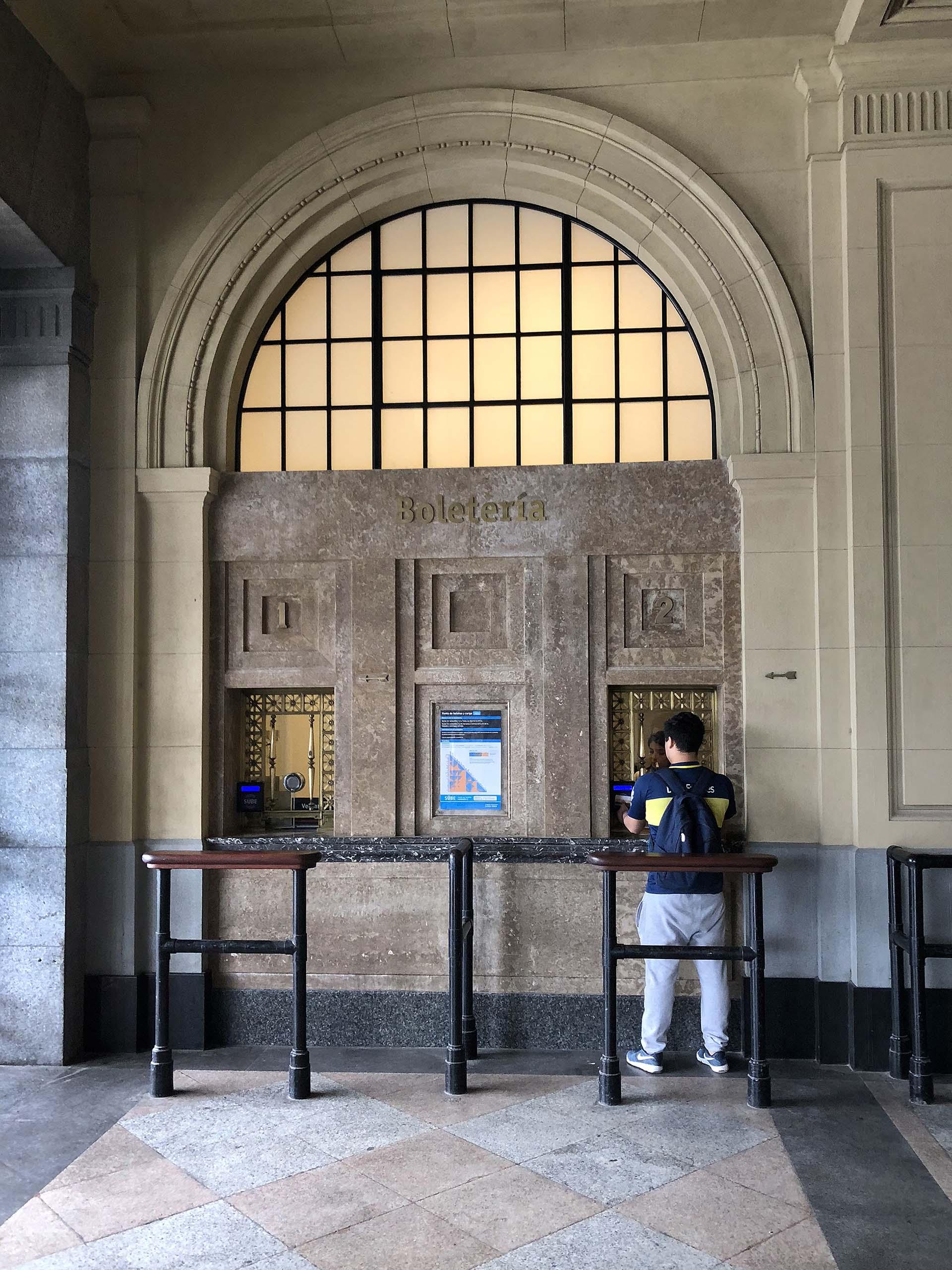 Estación Constitución, un domingo por la tarde, un hincha de Boca carga su SUBE para ir a la Bombonera. Una imagen clásica que descubre además la identidad futbolera del artista