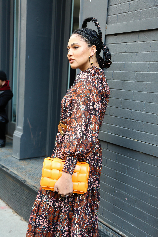 Maxi vestido estampado, con mangas abullonadas y cuello cerrado, con cinturón, y clutch acolchonado en color amarillo, Ayesha Curry, una blogera fue al desfile de Ulla Johnson con un peinado llamativo