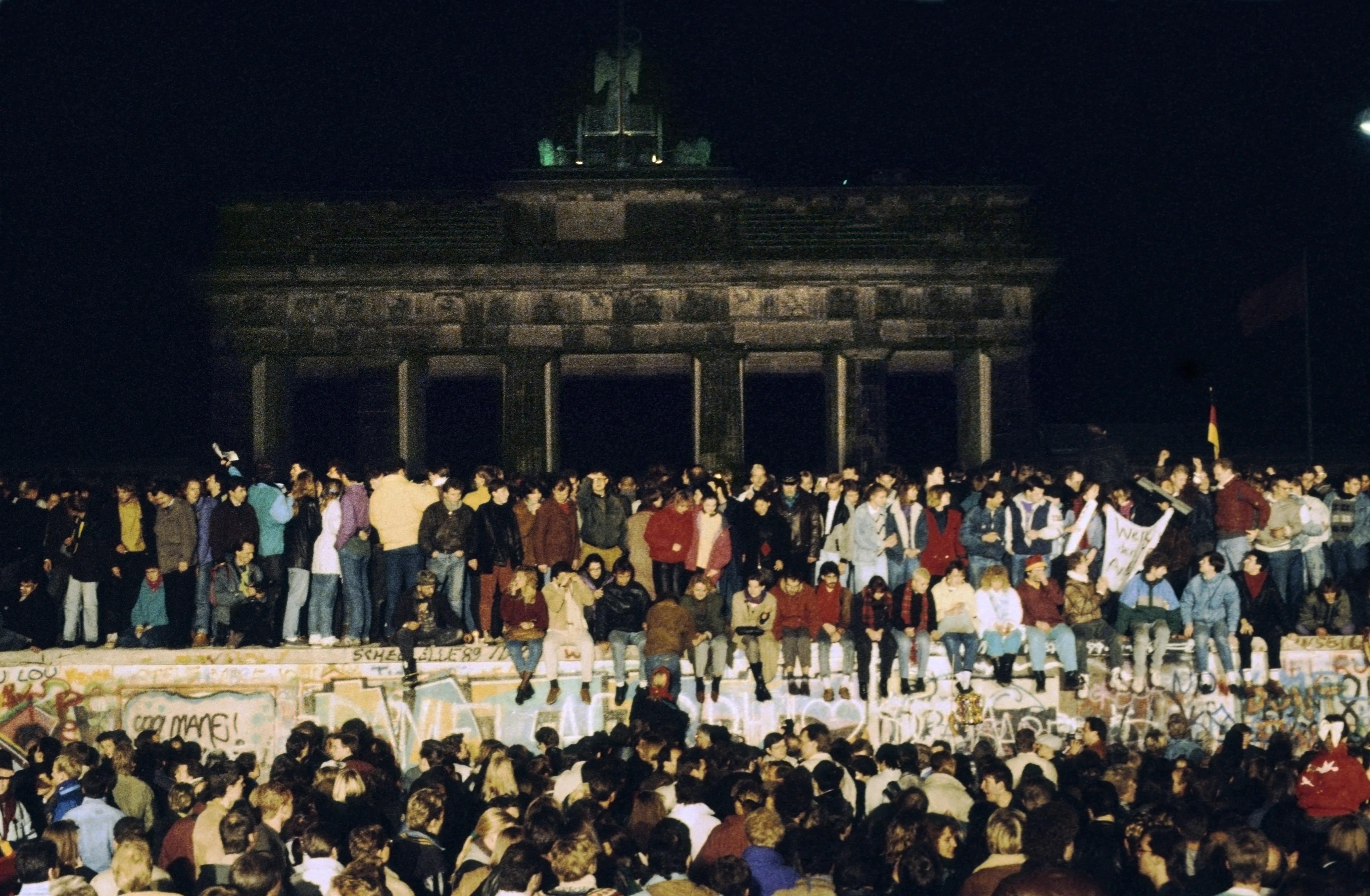 Miles de jóvenes se trepan al muro en la noche del 9 de noviembre de 1989. Los guardias no están a la vista. La pared todavía está de pie, pero el muro ha caído.