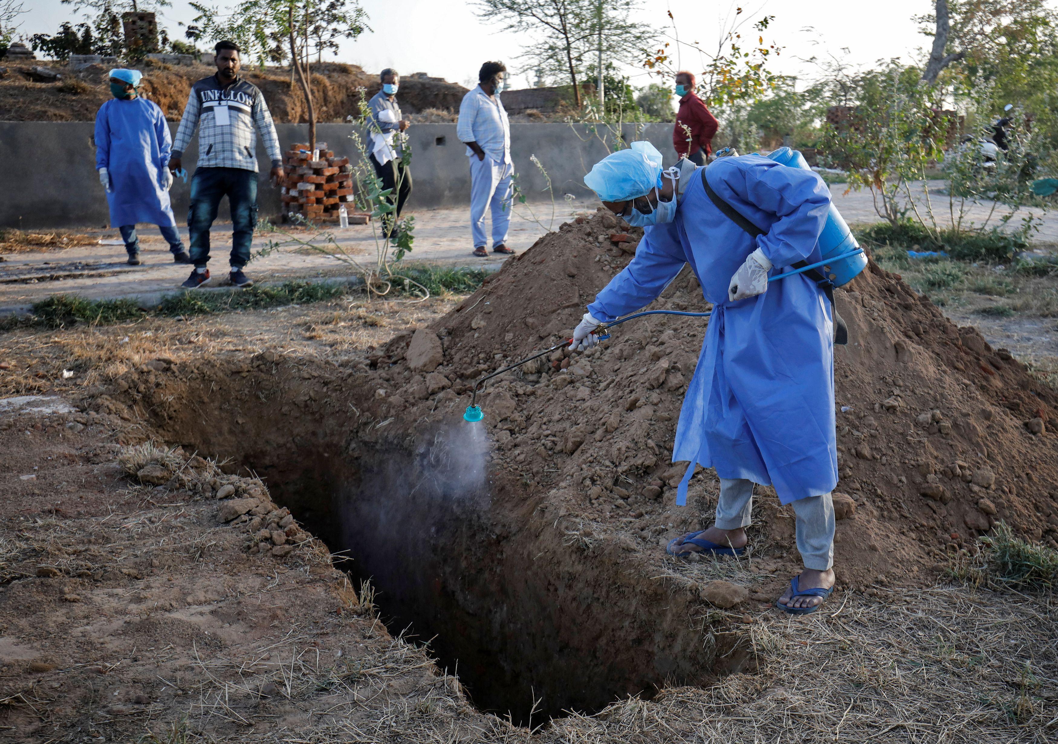 Un trabajador municipal desinfecta la fosa donde descansará el cuerpo de una persona que murió por coronavirus en la India (REUTERS/Amit Dave)