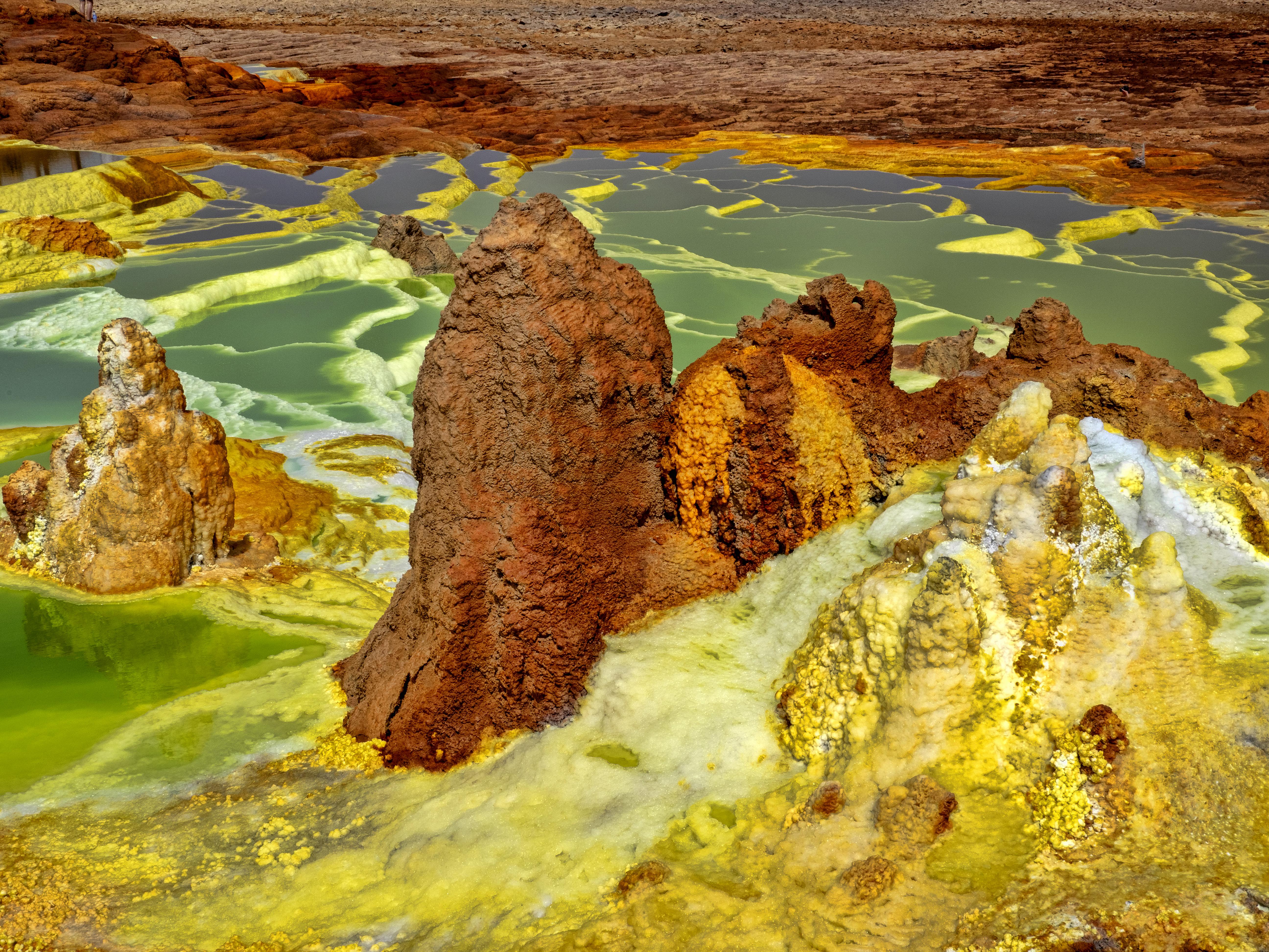 La Depresión de Danakil en Etiopía y su paisaje, que consiste en sal ardiente, roca volcánica y ácido sulfúrico, se considera el lugar más inhabitable de la Tierra. Los manantiales alrededor del volcán Dallol, uno de los numerosos volcanes dentro de la Depresión, tienen propiedades hidrotermales que no solo son tóxicas sino que también no son adecuadas para la vida