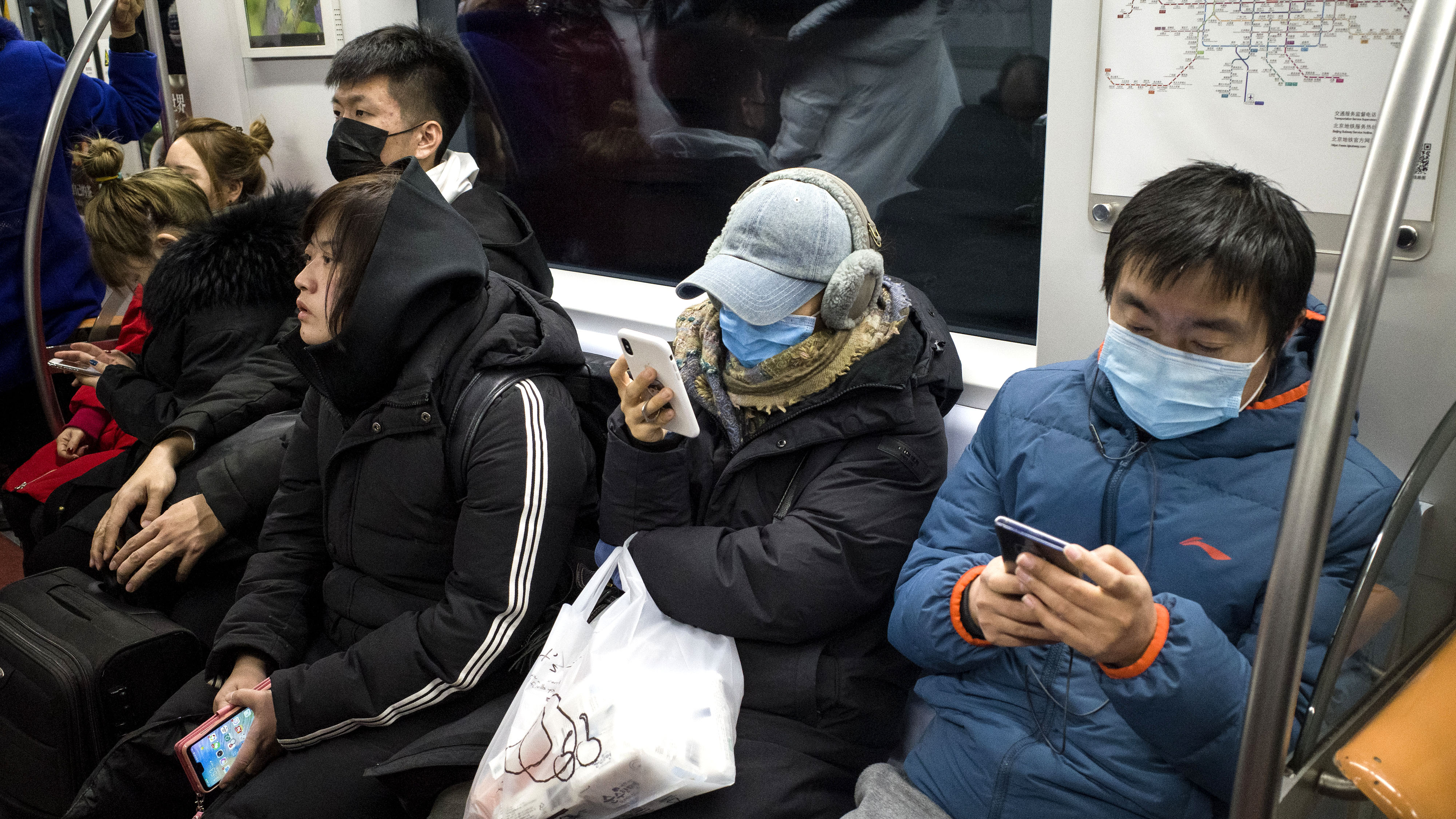 Los pasajeros del metro usan máscaras protectoras en Beijing el 21 de enero de 2020. - El número de muertos por un nuevo virus de China que es transmisible entre humanos aumentó a seis, dijo el alcalde de Wuhan en una entrevista con la cadena estatal CCTV el 21 de enero. La Organización de la Salud dijo que consideraría declarar una emergencia internacional de salud pública sobre el brote. (Foto por NOEL CELIS / AFP)