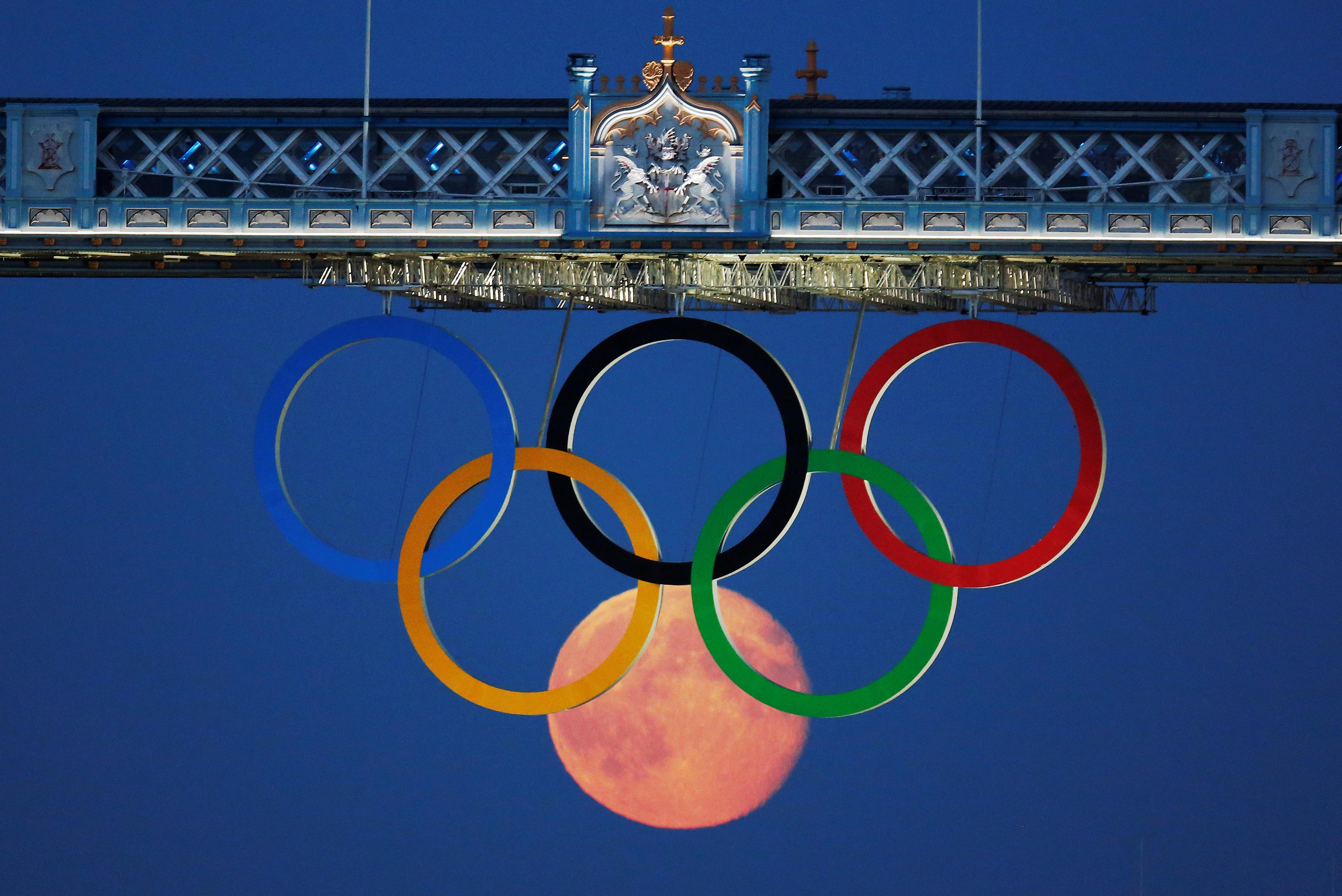 La luna llena se aprecia a través de los Anillos Olímpicos que cuelgan bajo el Puente de la Torre durante los Juegos Olímpicos de Londres 2012, el 3 de agosto de 2012 (REUTERS/Luke MacGregor)
