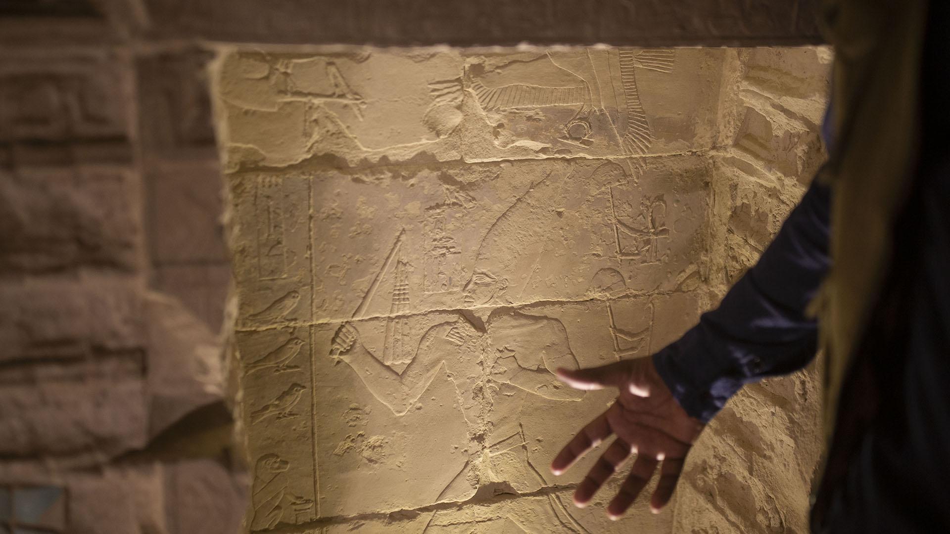 El arqueólogo Ragab Dawood describe una talla de piedra mientras realiza un recorrido por la pirámide escalonada en Saqqara, Egipto, que se abrió para los visitantes el jueves 5 de marzo de 2020 (AP)