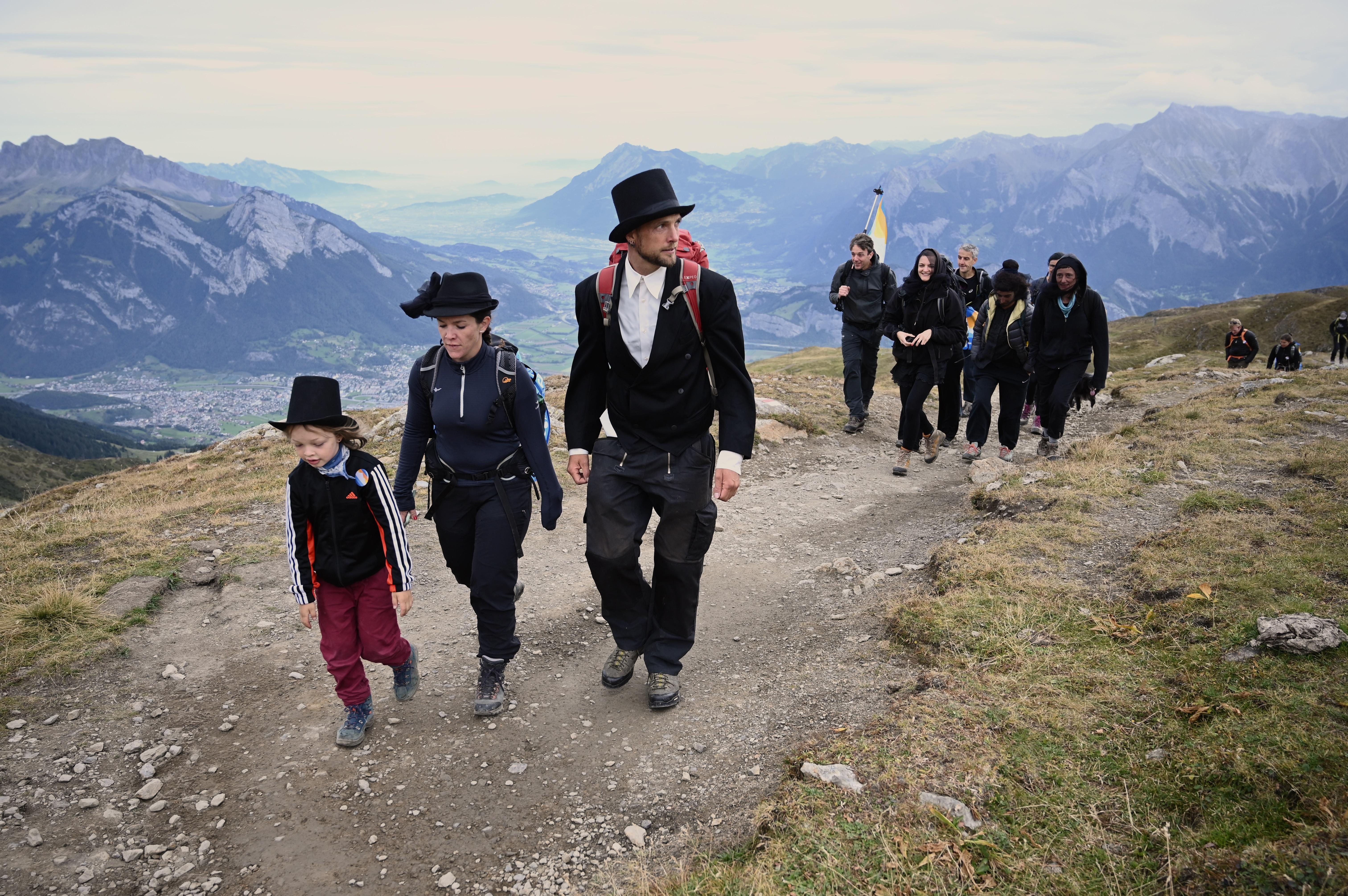 Vestidos de negro y con sombreros, la gente participa en el