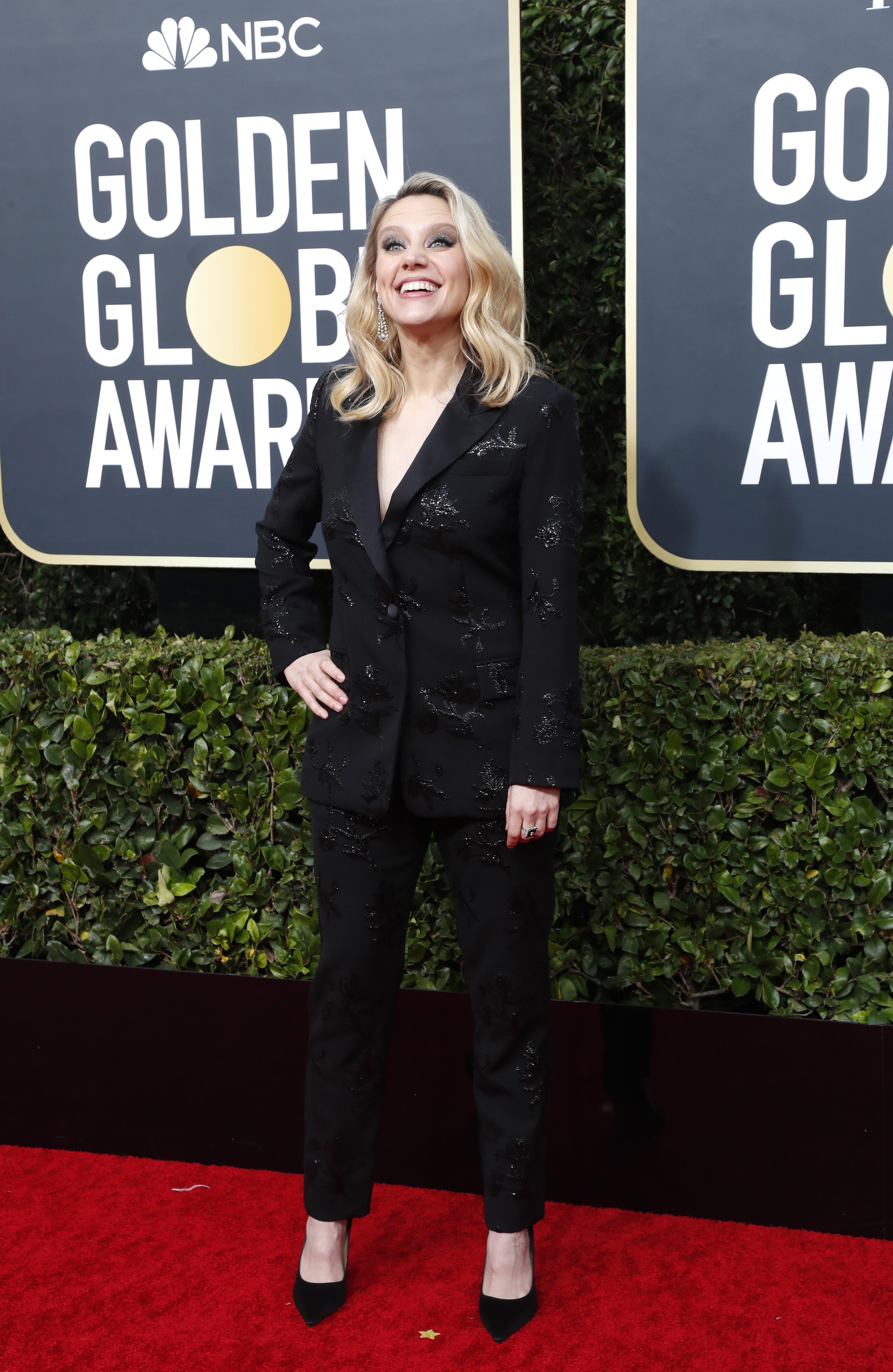 Kate McKinnon apostó a un look masculino y lució un esmoquin negro con detalles de paillettes. Completó su look con stilettos negros en punta de chiffón y aros gota