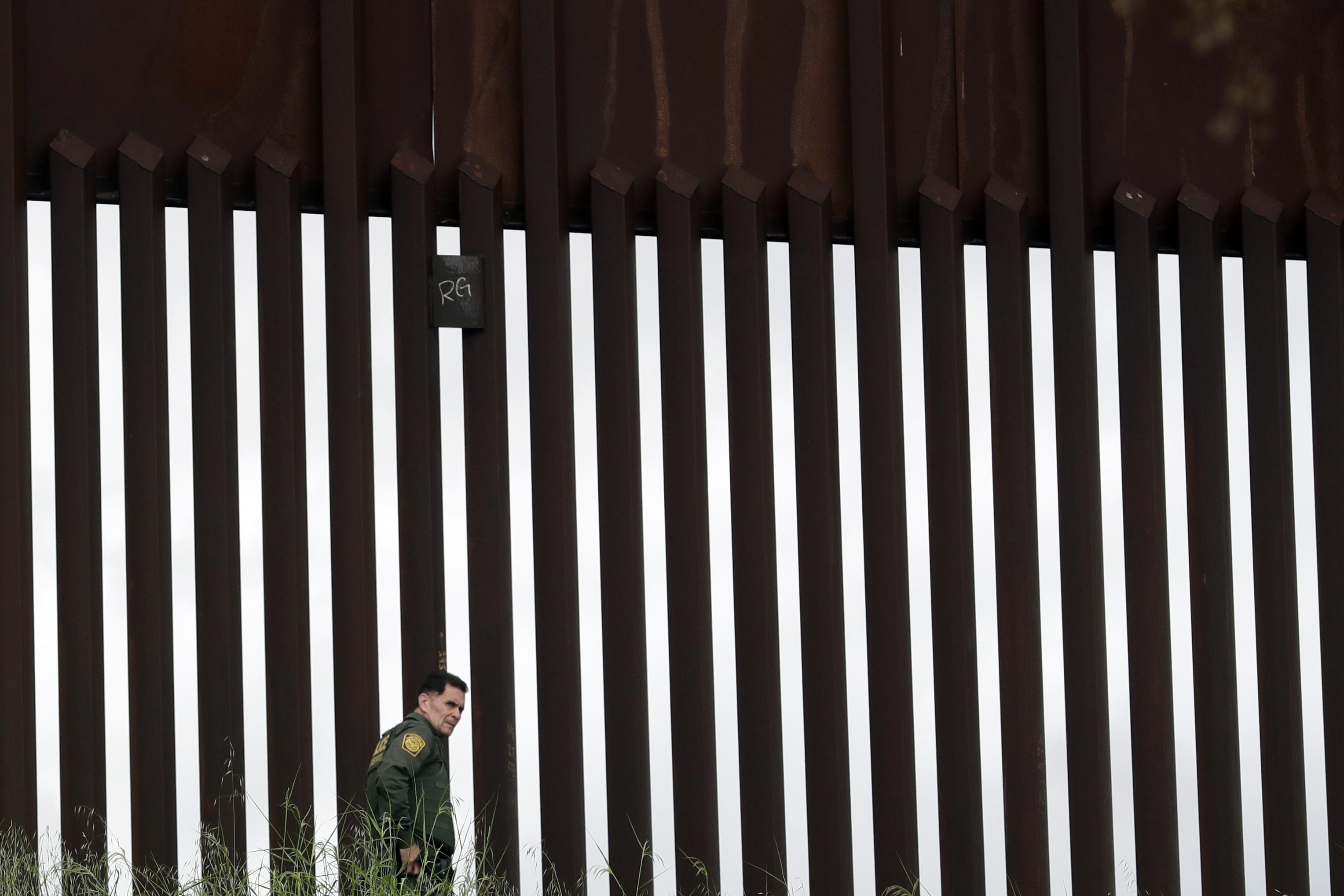 Un agente de la patrulla fronteriza camina a lo largo de un muro fronterizo que separa a Tijuana, México, de San Diego, el miércoles 18 de marzo de 2020 en San Diego.