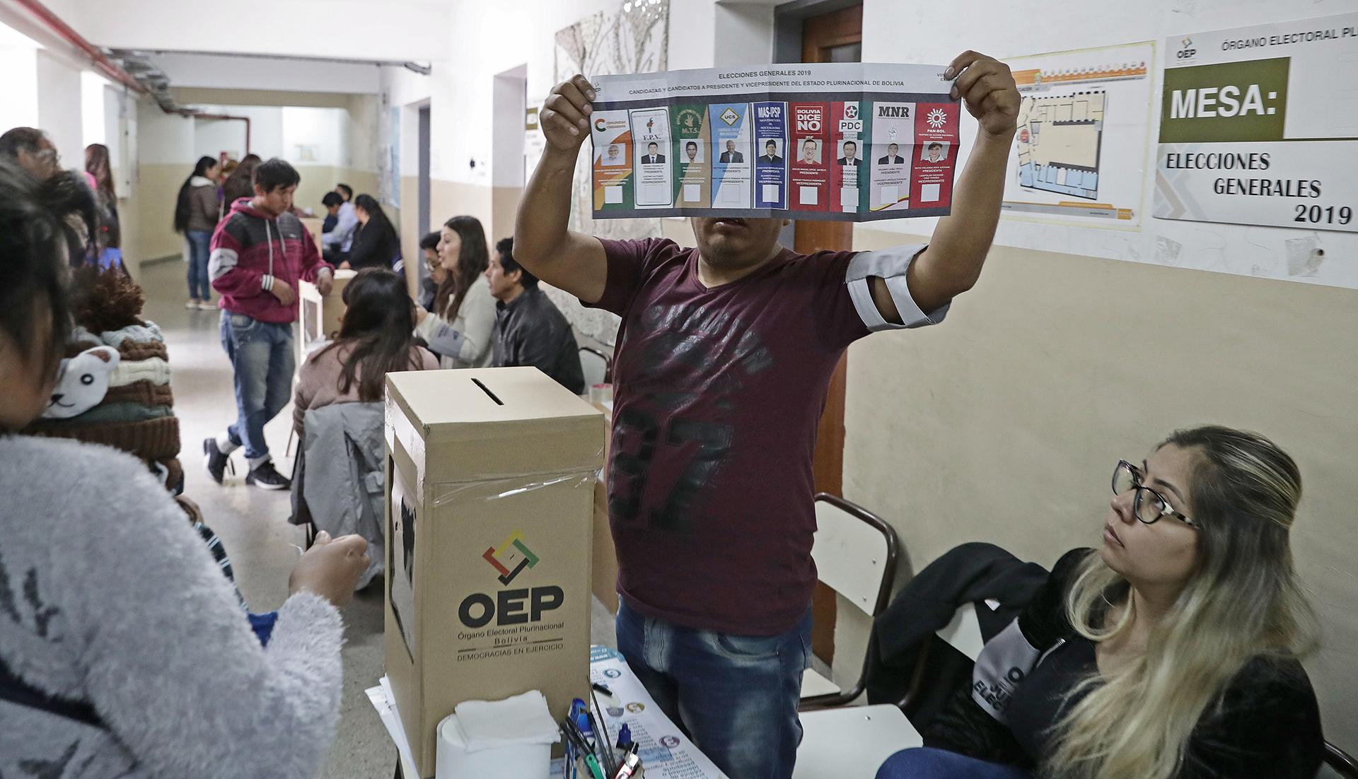 Una de las autoridades de mesa muestra la boleta a los ciudadanos bolivianos residentes en Buenos Aires que se preparar para emitir su voto
