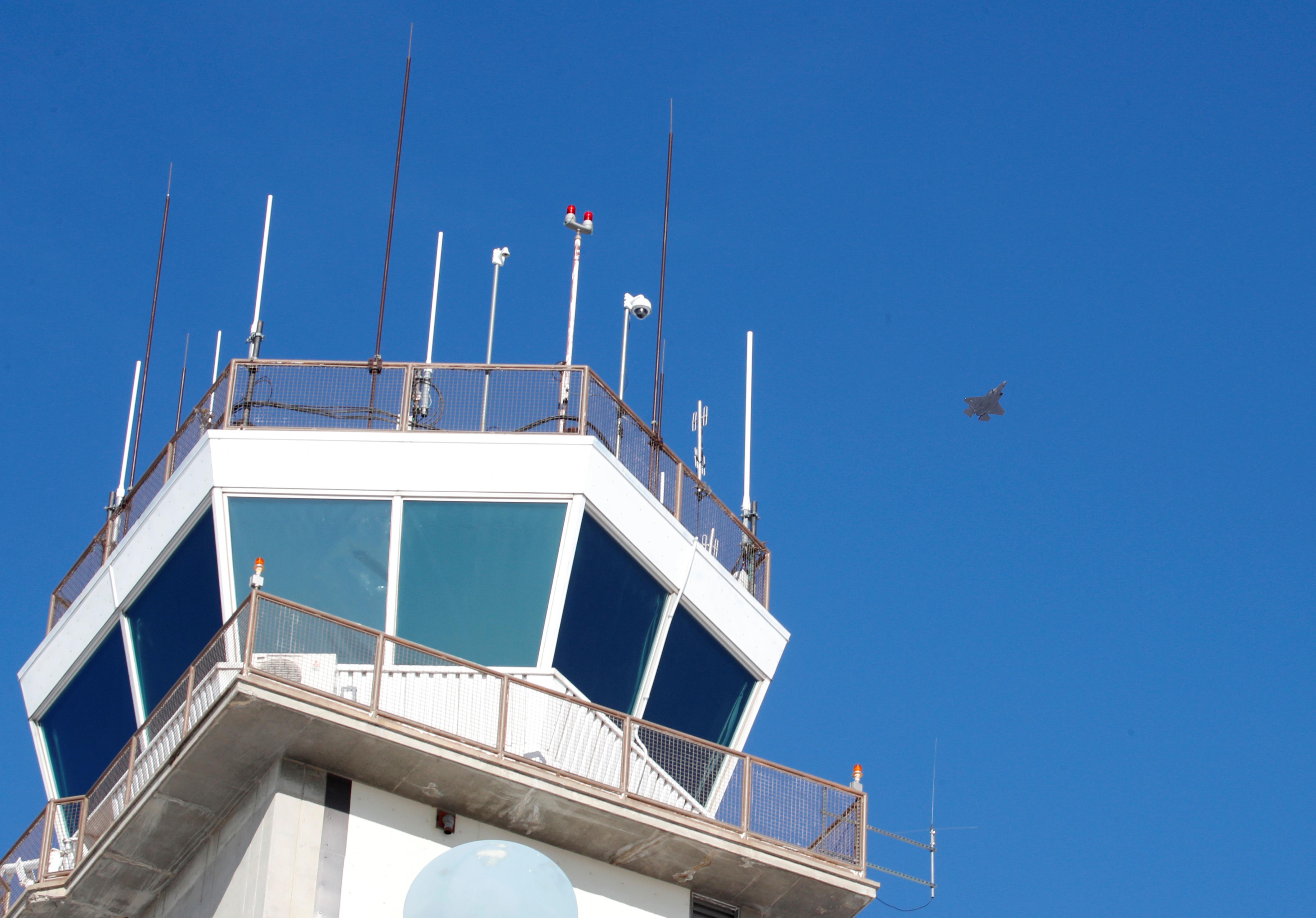 La torre de control de la Base Aérea Hill, en Utah. Detrás, un F-35 atraviesa el cielo (Reuters)