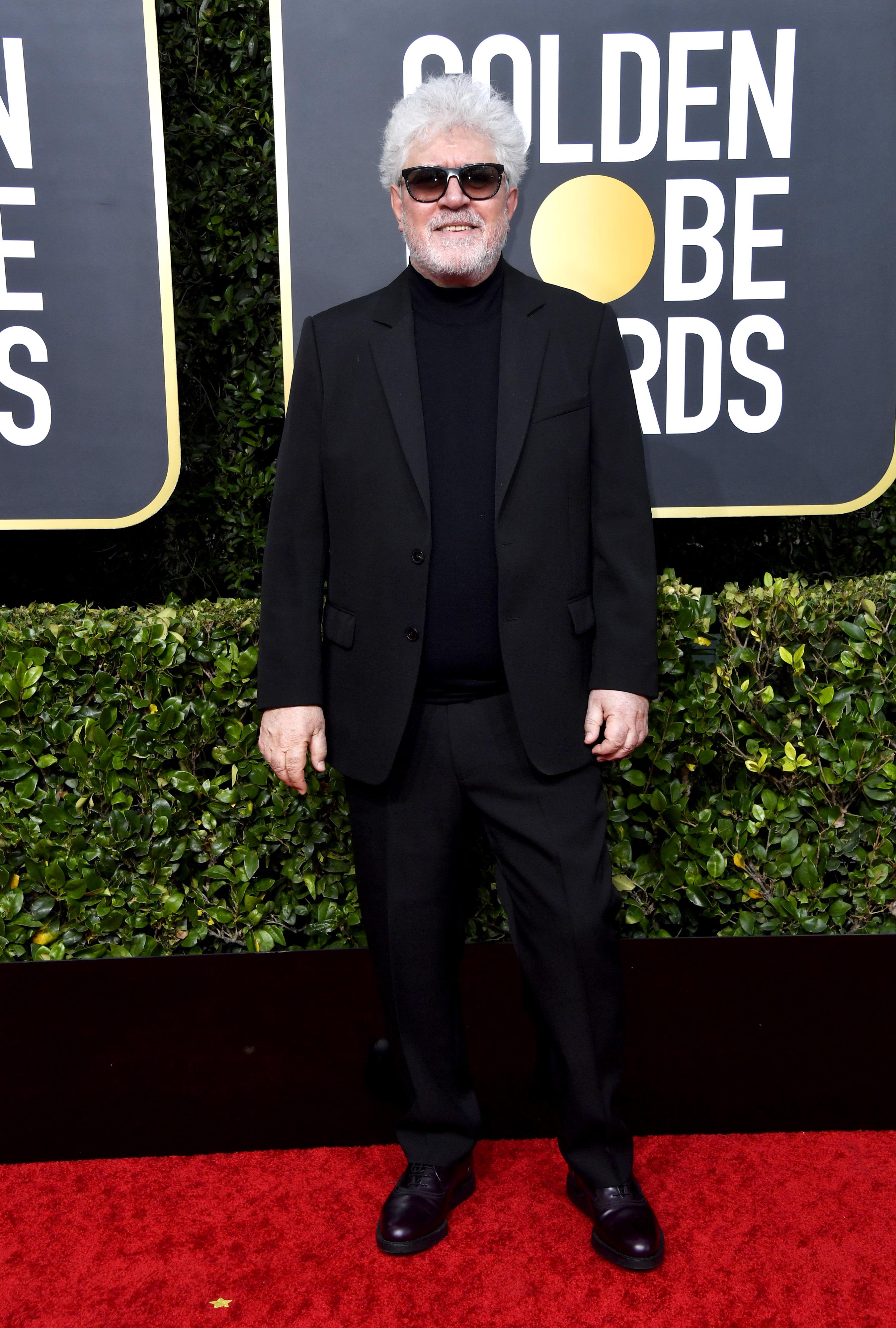 Pedro Almodóvar eligió para la red carpet de los Golden Globe un traje negro pero a diferencia de una camisa optó por una polera negra. Como complemento, llevó sus características gafas negras