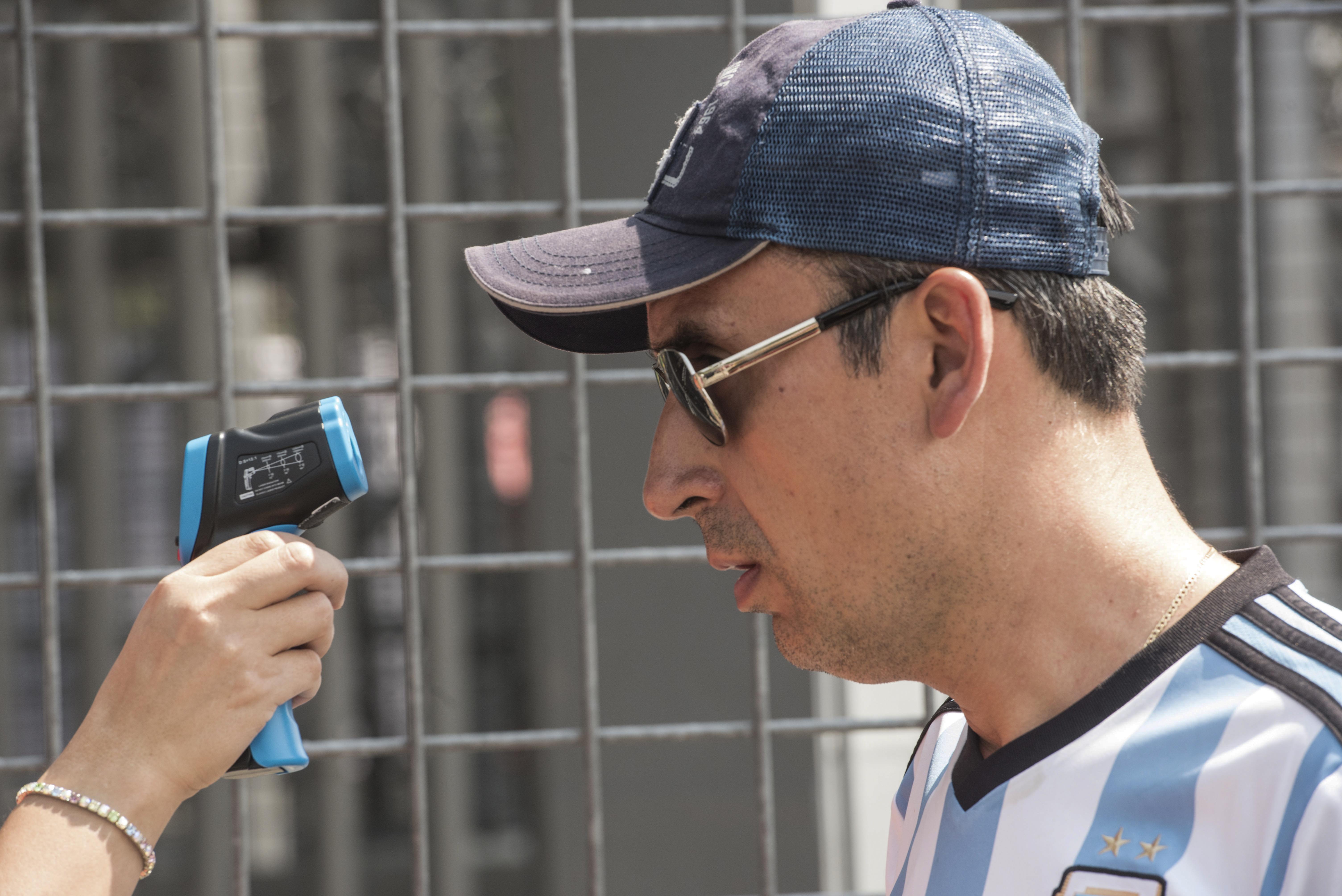 El personal de salud verifica la temperatura de un asistente al festival de música 'Vive Latino' como medida preventiva frente a la pandemia mundial de coronavirus COVID-19, en la Ciudad de México, el 14 de marzo de 2020.