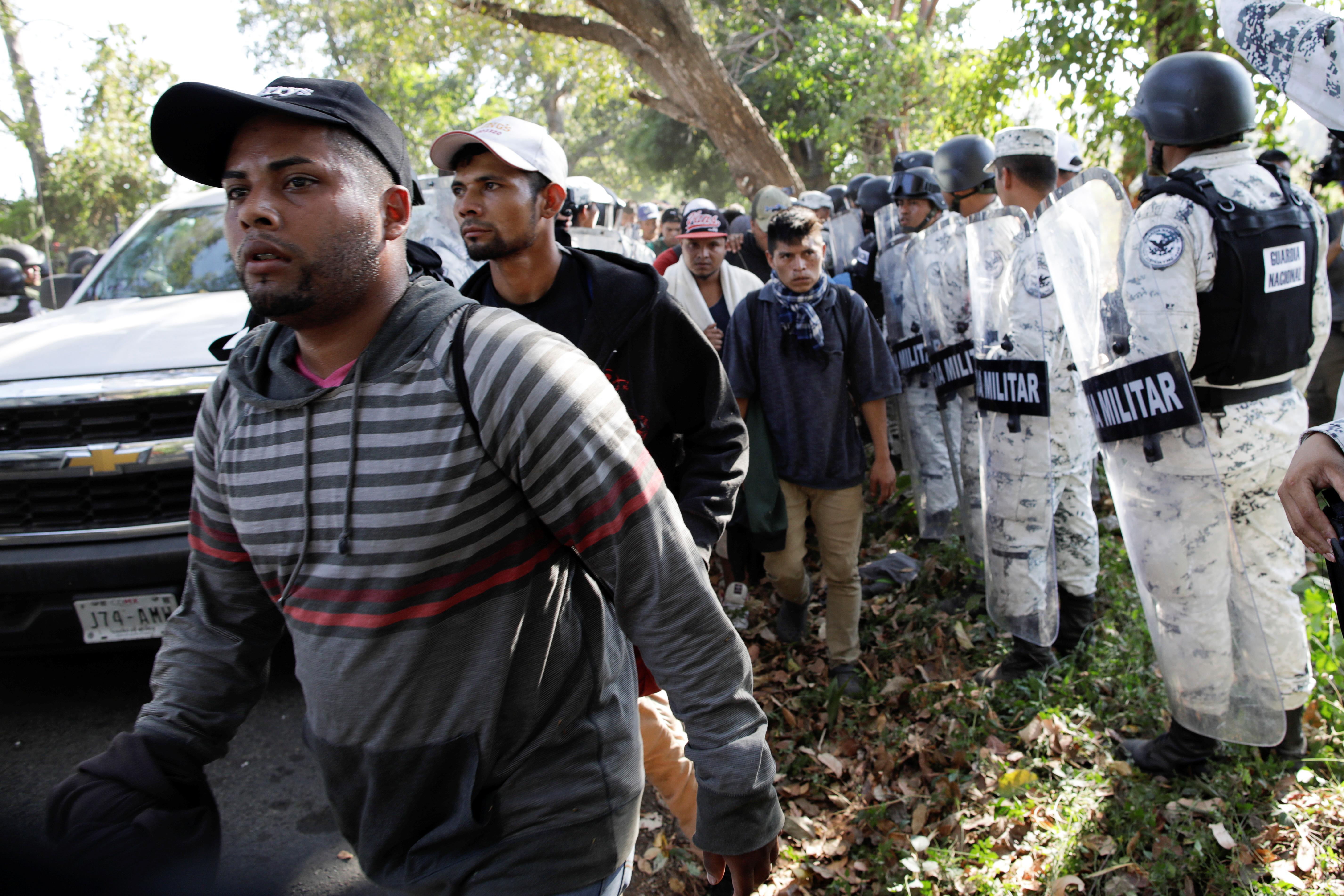 Elementos de la Guardia Nacional vigilan a los migrantes mientras se dirigen a los autobuses para ser deportados (Foto: Andrés Martínez Casares/Reuters)