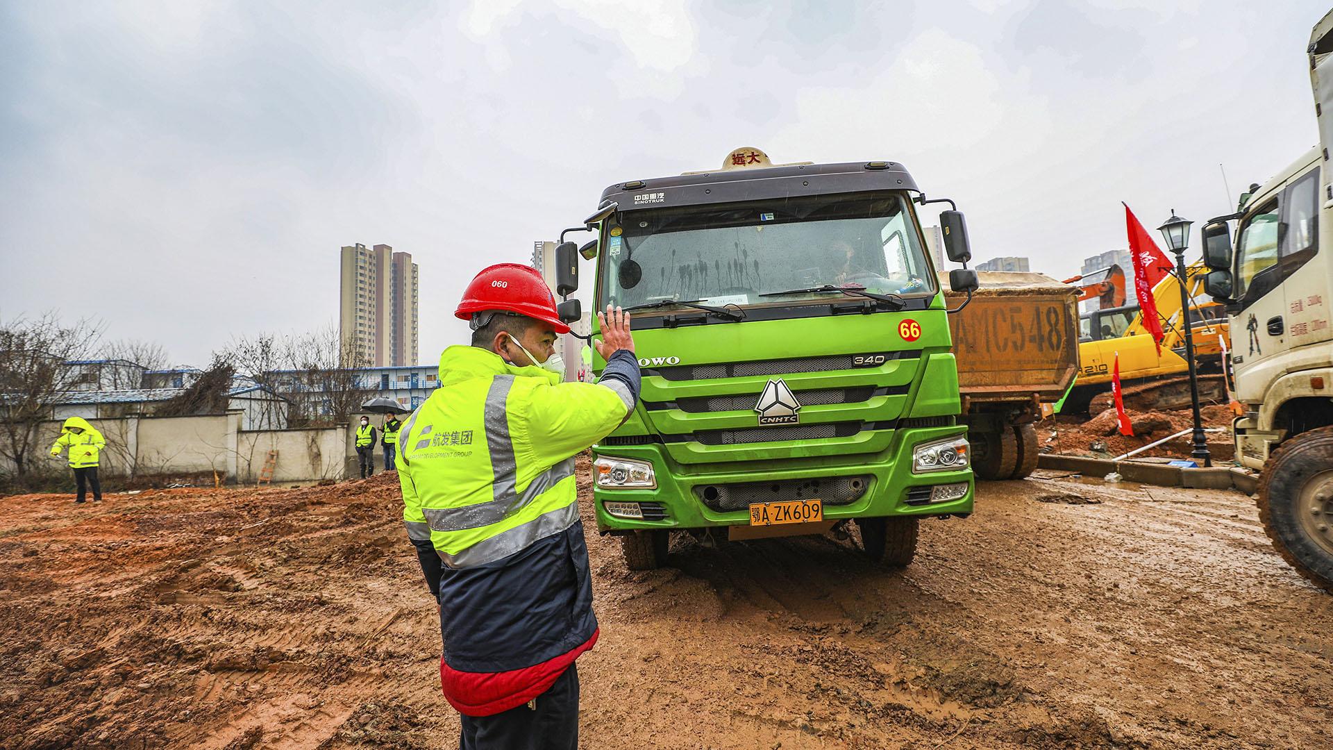 Un trabajador hace un gesto a un camionero en un sitio de construcción para un hospital de campaña en Wuhan, en la provincia central china de Hubei, el viernes 24 de enero de 2020. (Chinatopix vía AP)