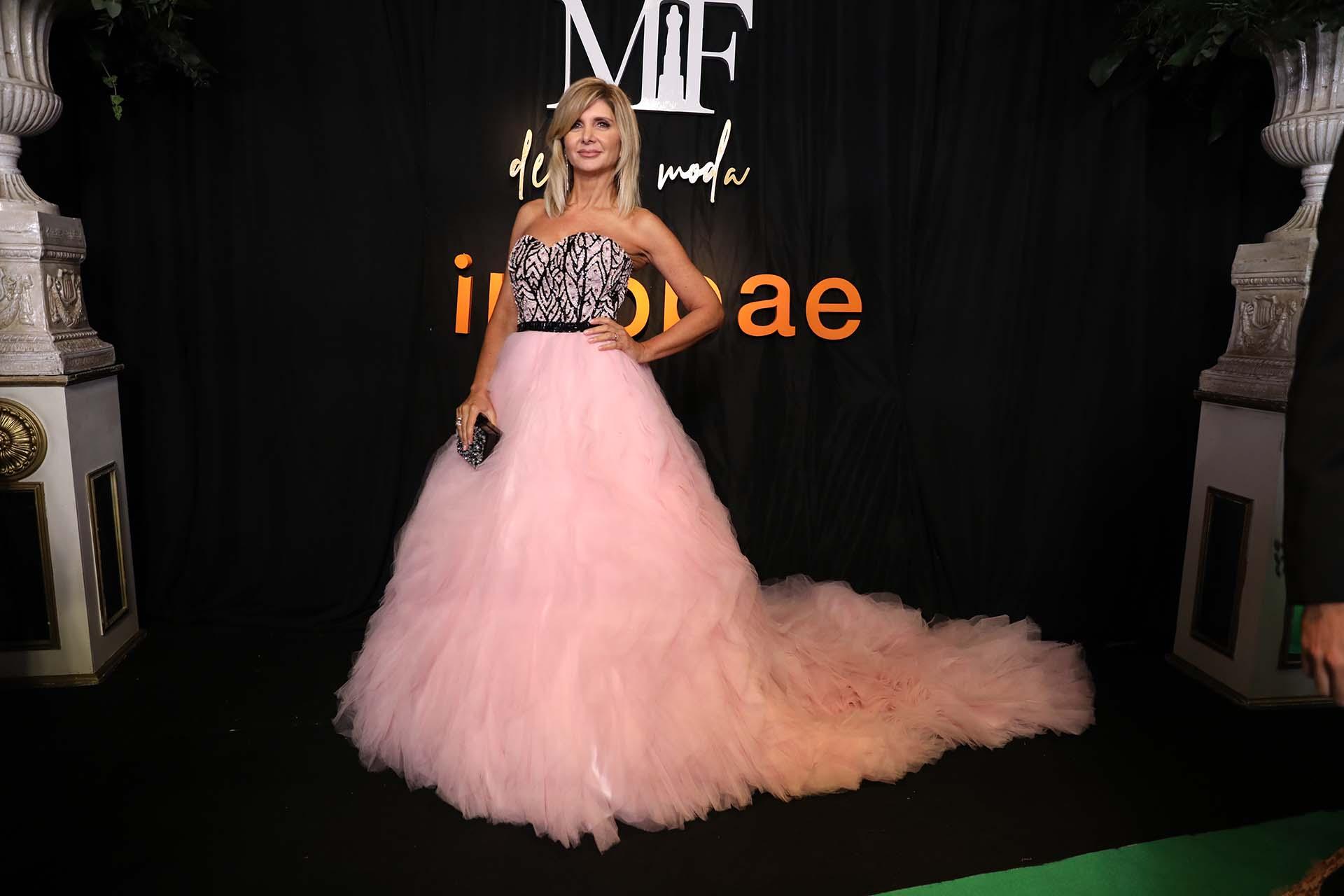 La periodista Debora Plager, vestida por Claudio Cosano con un vestido rosa y negro, con una gran cola, joyas de Bartolomé que acompañan en armonía el diseño