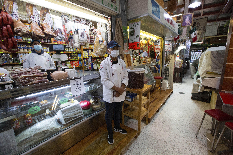 Los vendedores con máscaras protectoras esperan a los compradores en el popular mercado de alimentos de San Juan en la Ciudad de México, el miércoles 25 de marzo de 2020.