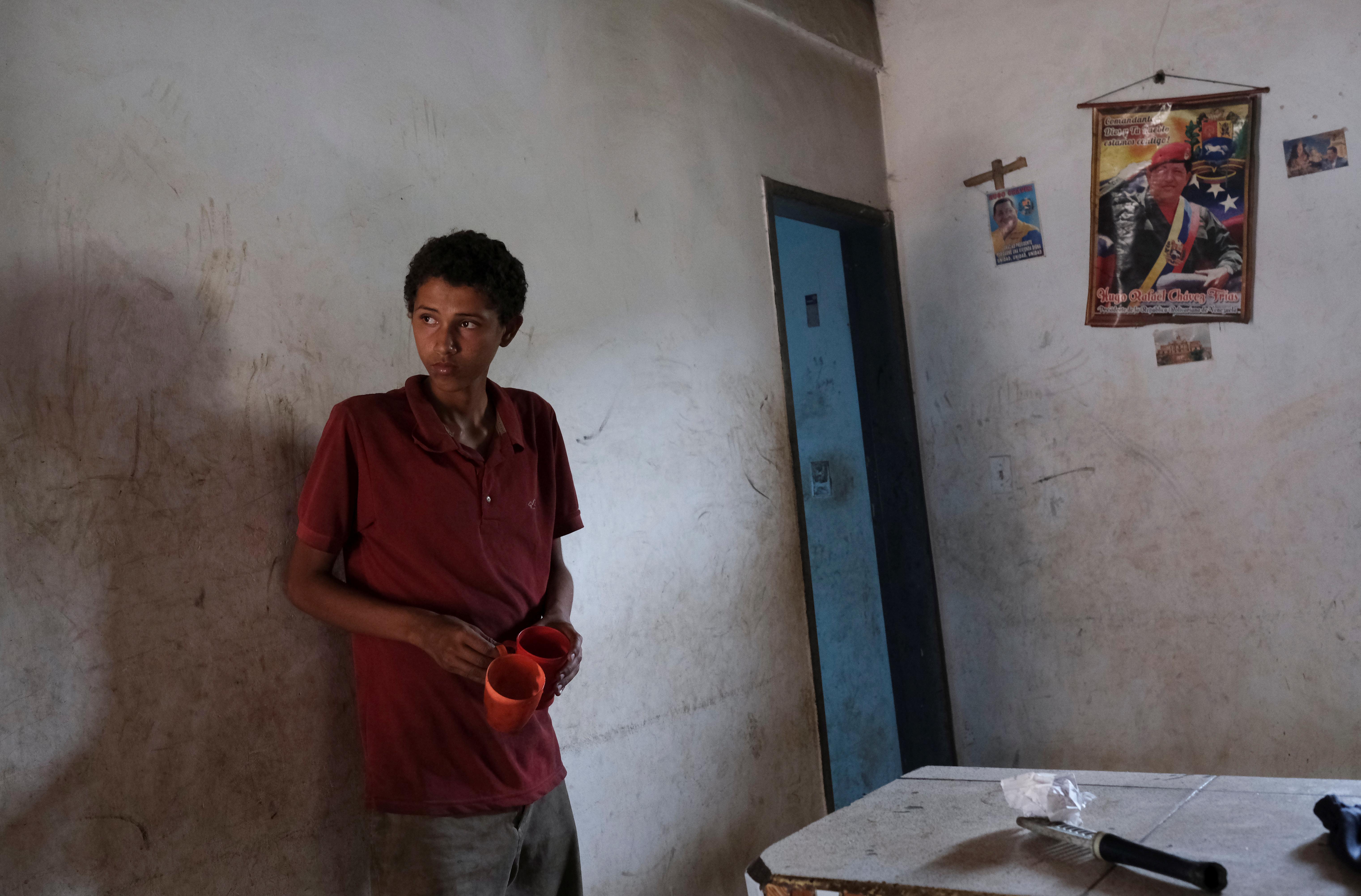 Carlos Flores, de 15 años, que tiene bajo peso por su estatura, según su madre, Blanca Naveda, se para frente a fotos del fallecido presidente de Venezuela, Hugo Chávez, en su casa en Barquisimeto (REUTERS/Carlos García Rawlins)