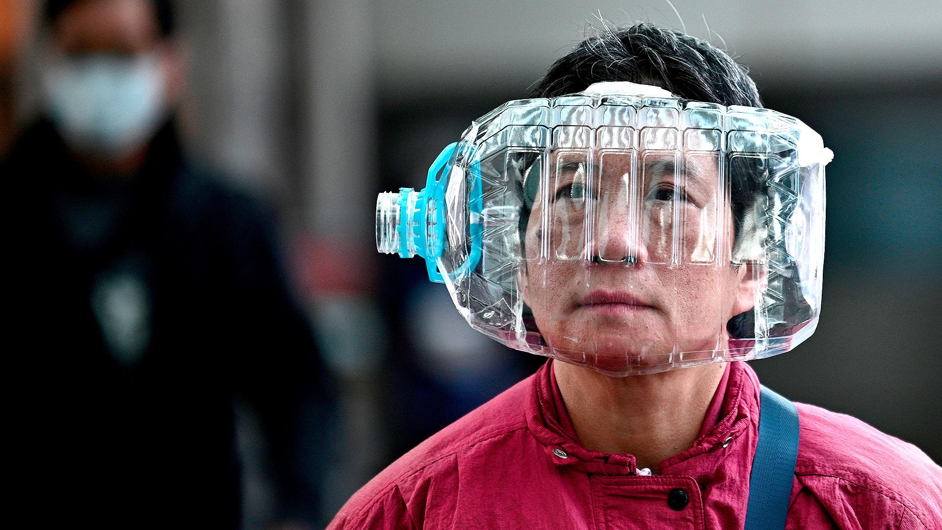 Una mujer usa una botella de agua de plástico con un recorte para cubrirse la cara, mientras camina por una pasarela en Hong Kong el 31 de enero de 2020, como medida preventiva después de un brote de virus que comenzó en la ciudad china de Wuhan (Anthony WALLACE / AFP)
