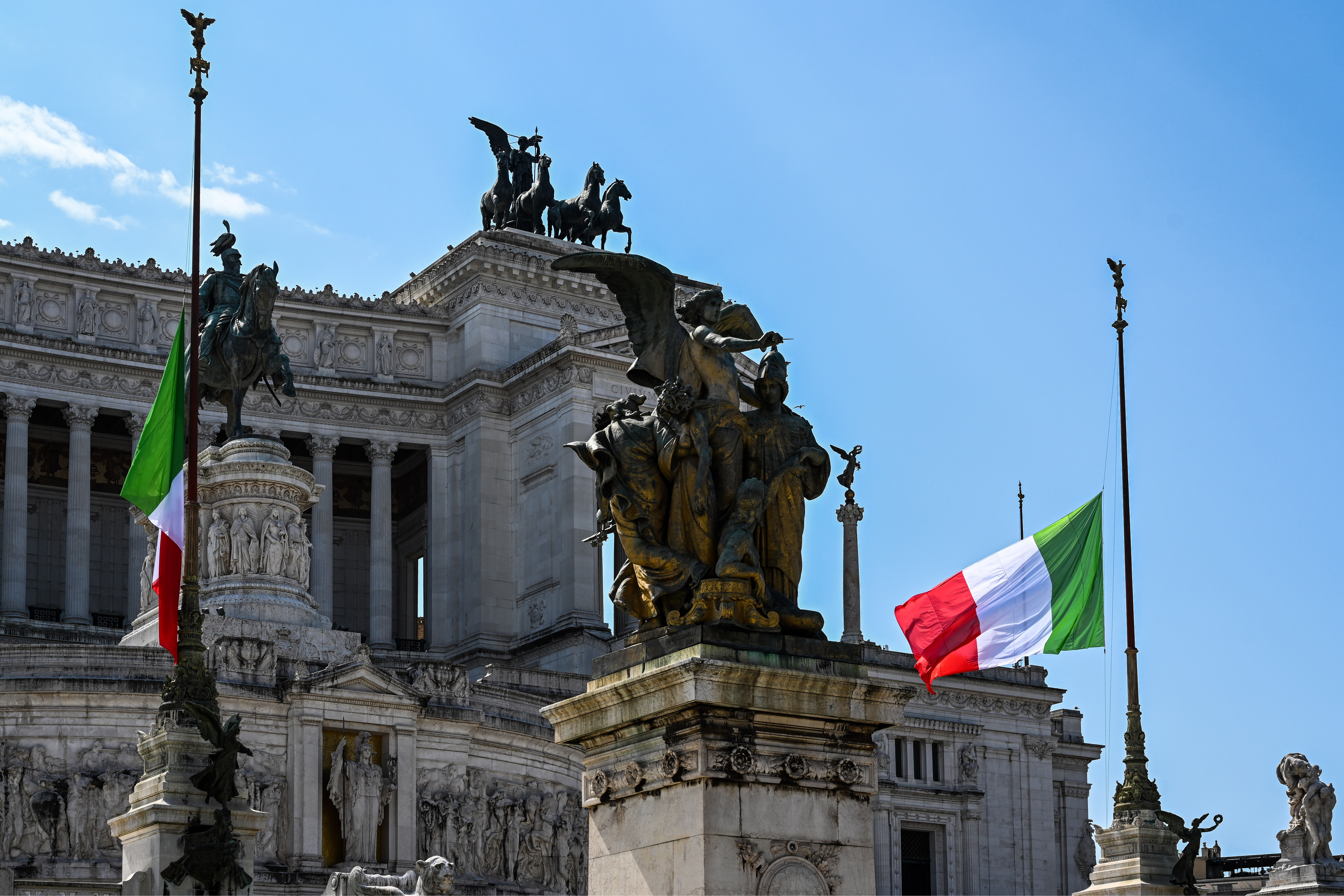 Banderas italianas flamean a media asta en el Altare della Patria-monumento Vittorio Emanuele II, ubicado en Roma, el 31 de marzo. Foto: Vincenzo PINTO / AFP