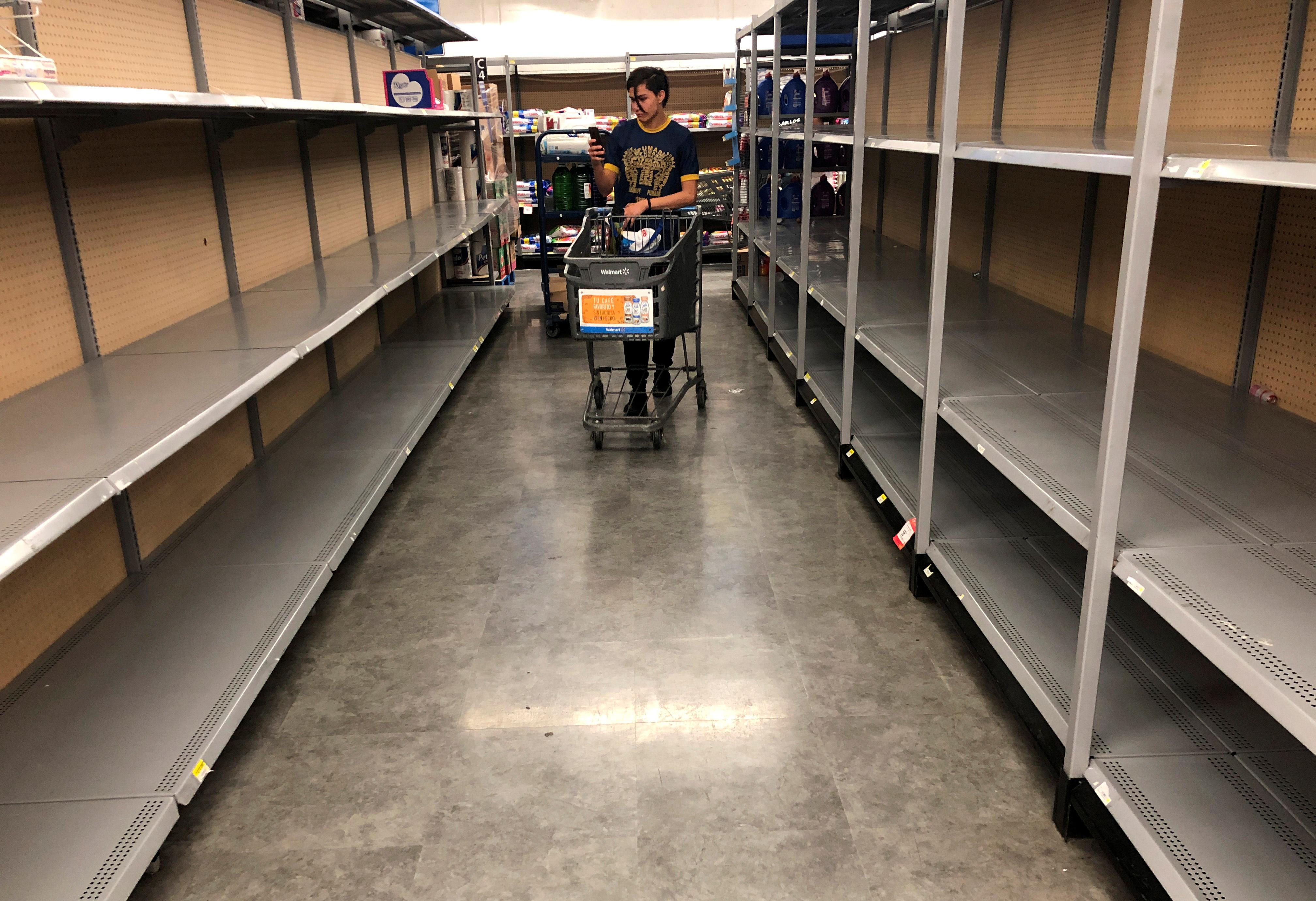 Un comprador filma estantes vacíos en un supermercado después de que las personas acapararan poductos de limpieza debido al brote de la enfermedad del coronavirus (COVID-19), en la Ciudad de México, México, 22 de marzo de 2020.