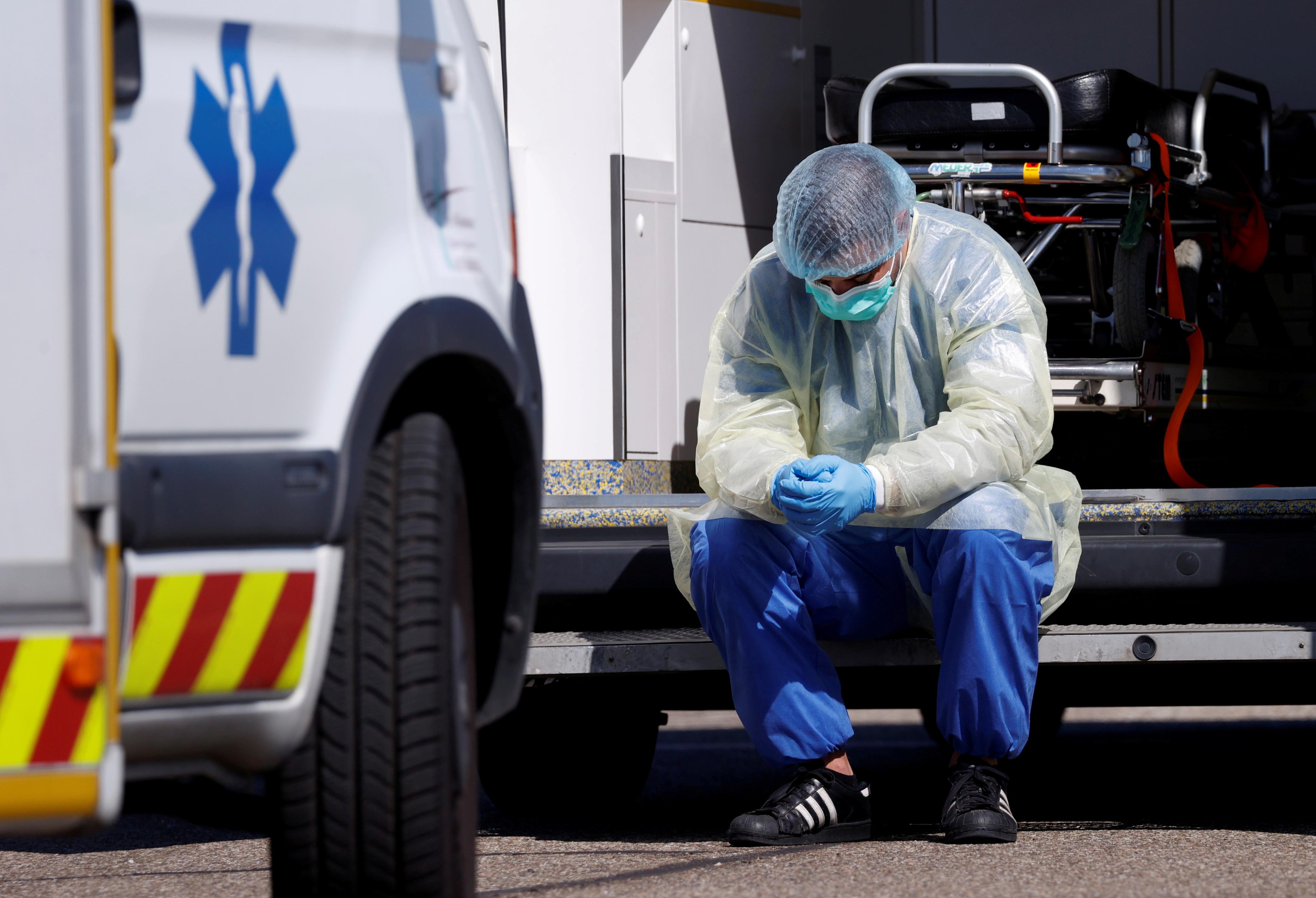 Un trabajador de la salud, que usa un equipo de protección, toma un descanso durante las operaciones de traslado de pacientes infectados en Francia (REUTERS/Christian Hartmann)