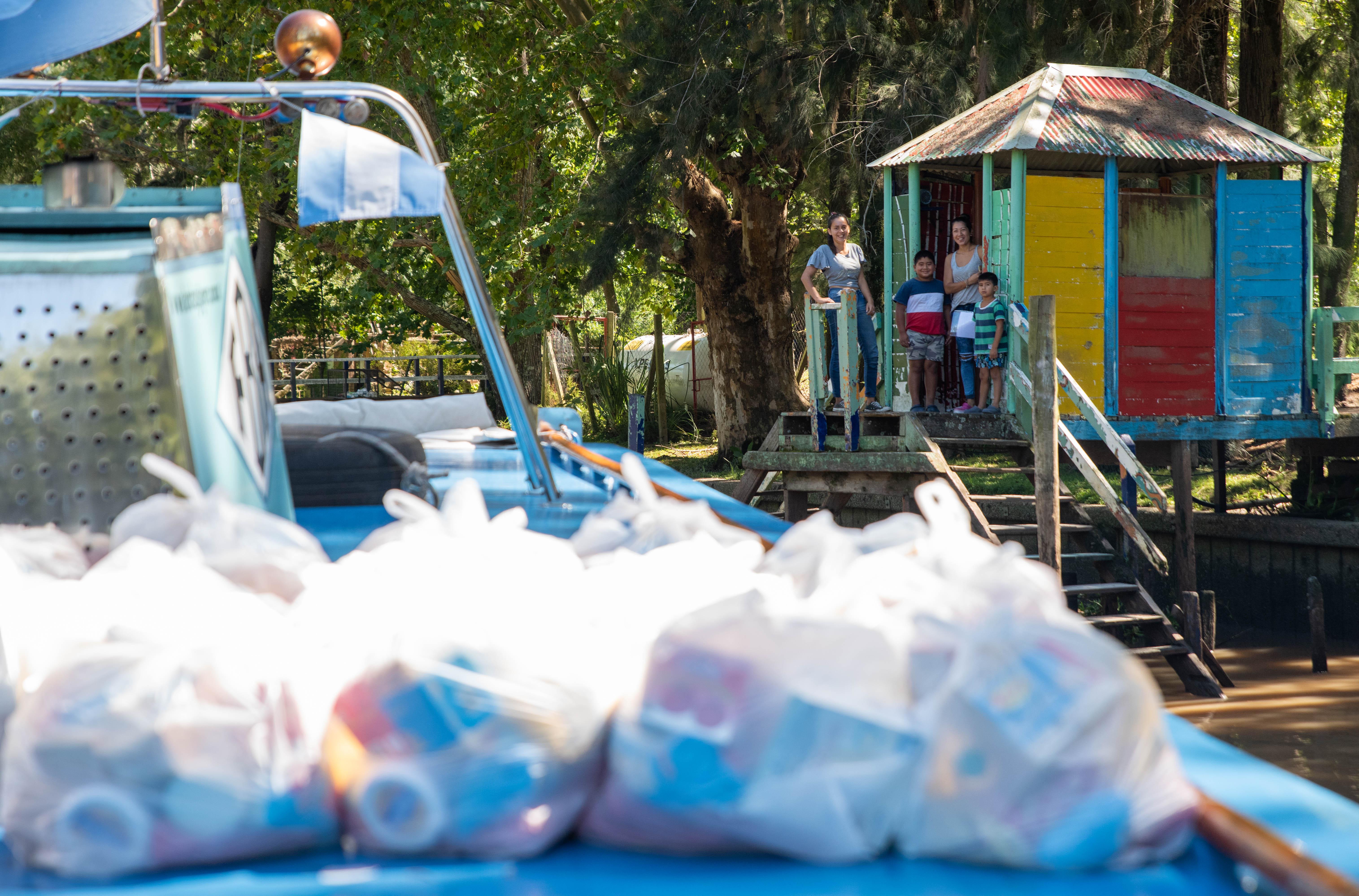 Una familia espera en el muelle, frente a su casa, que los docentes lleguen a entregarles los bolsones de alimentos y libros escolares. (Foto: Franco Fafasuli)