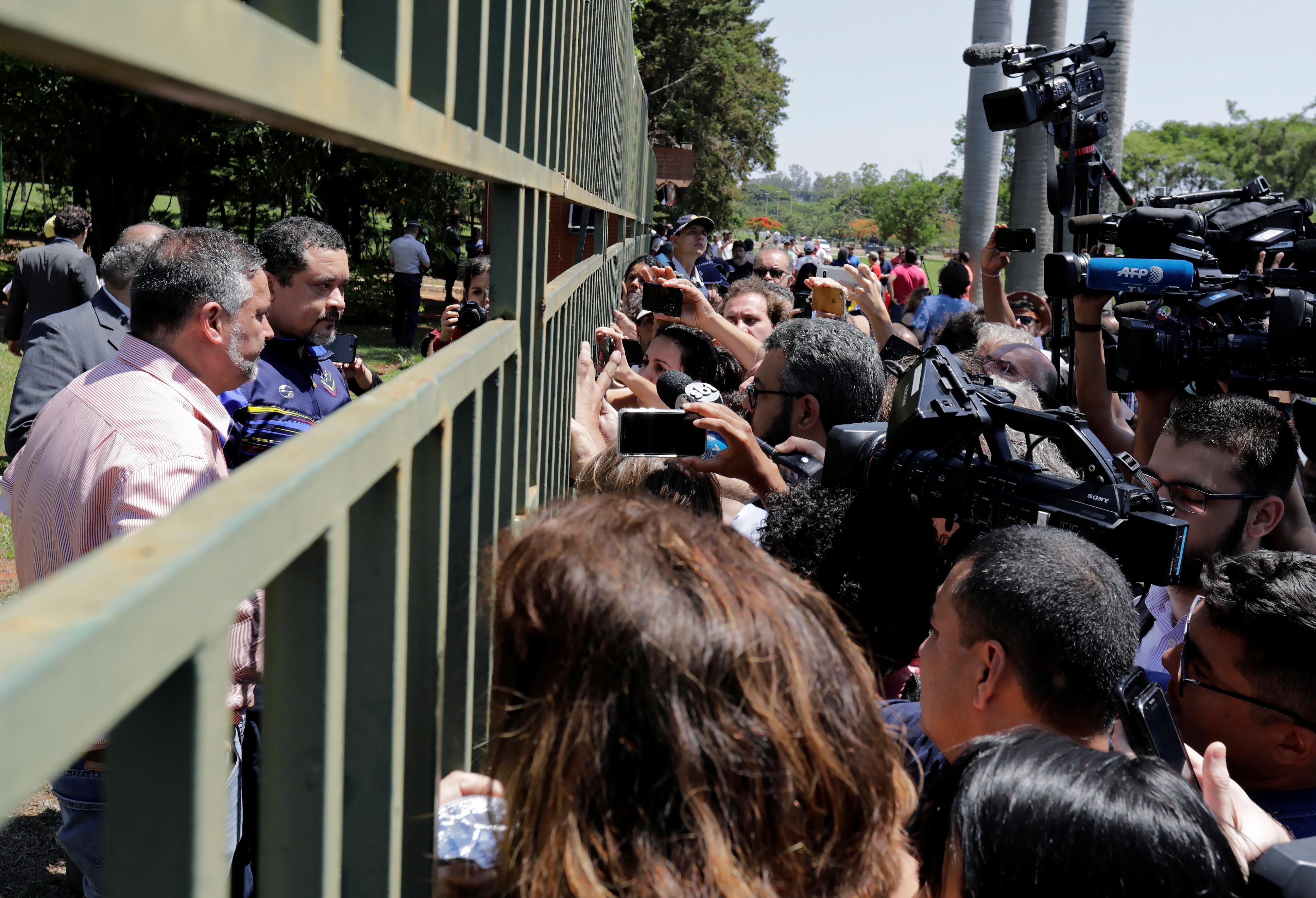 Empleados de la embajada de Venezuela hablan con periodistas que aguardan novedades en la puerta de la sede diplomática