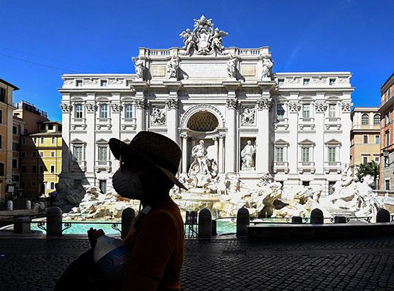 Una turista con un barbijo frente a la fontana di Trevi en el centro de Roma, el primer día del cierre de casi todas las actividades de país. (Foto de Vincenzo PINTO / AFP)
