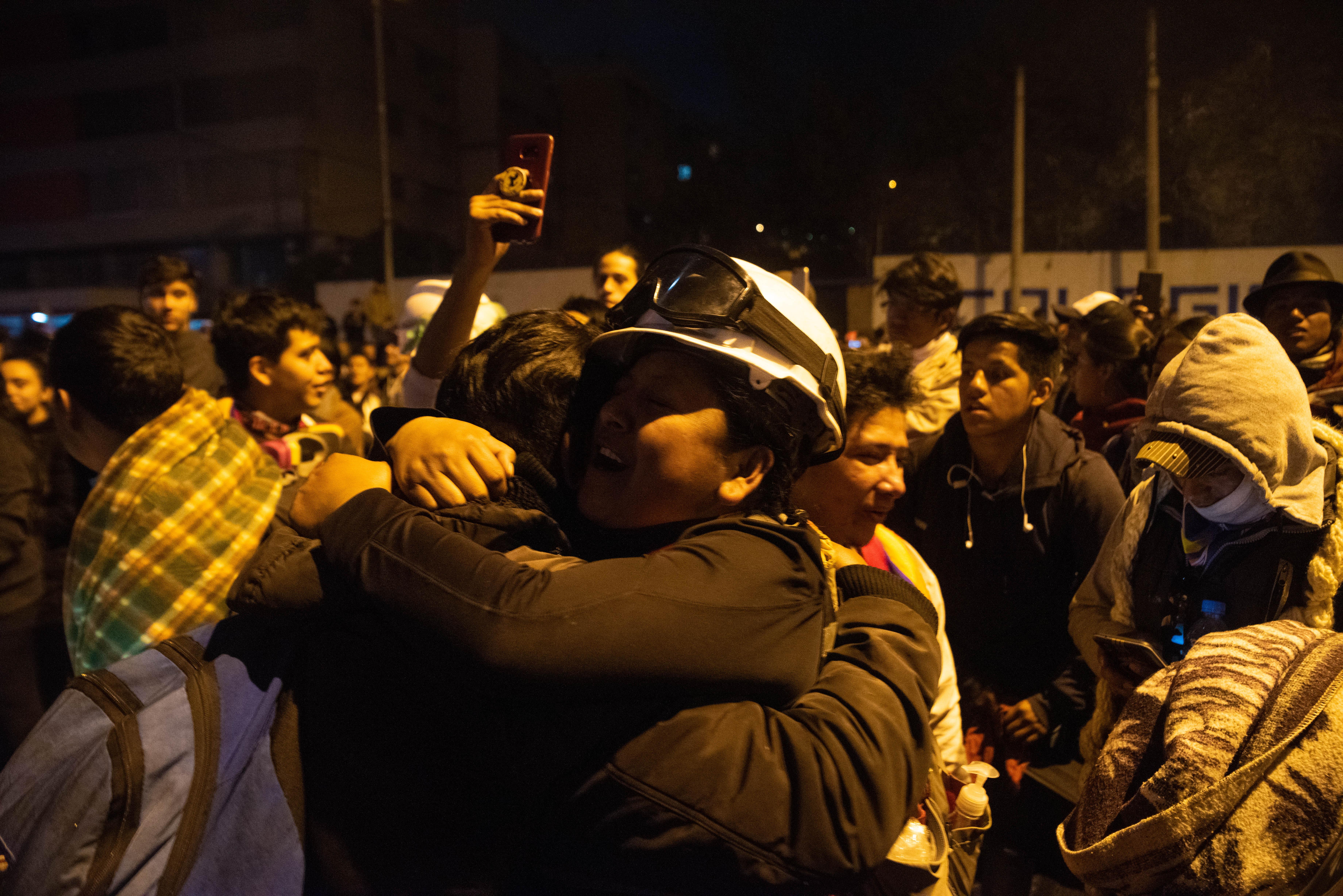 Un manifestante con casco y protección ocular se abraza con su compañeros en medio de los festejos por la derogación del Decreto 883 que eliminaba los subsidios a los combustibles.