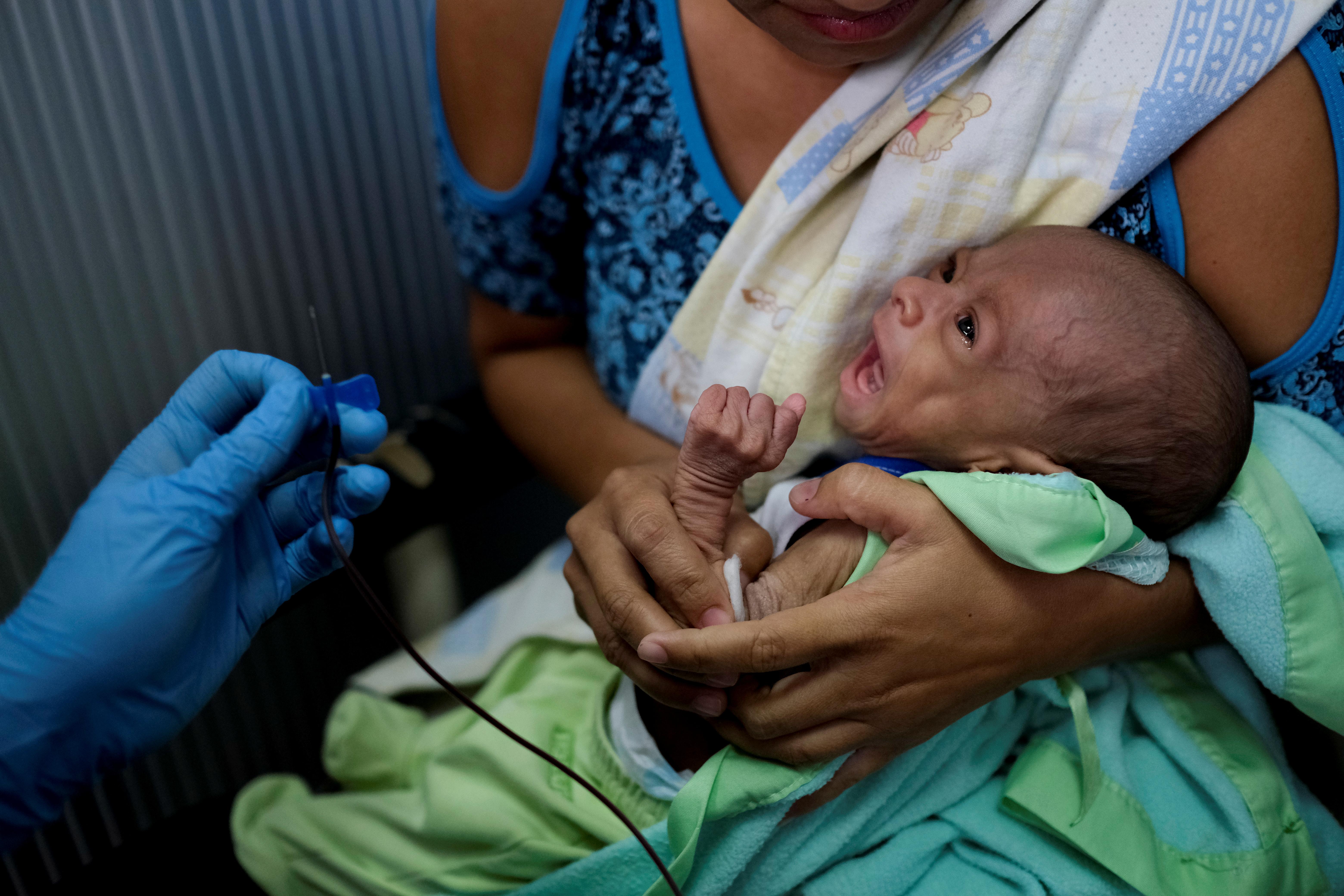 Francys Rivero sostiene a su hijo Kenai, de dos meses, a quien le diagnosticaron desnutrición, mientras le hacen un análisis de sangre en una clínica en Barquisimeto, Venezuela (REUTERS/Carlos García Rawlins)