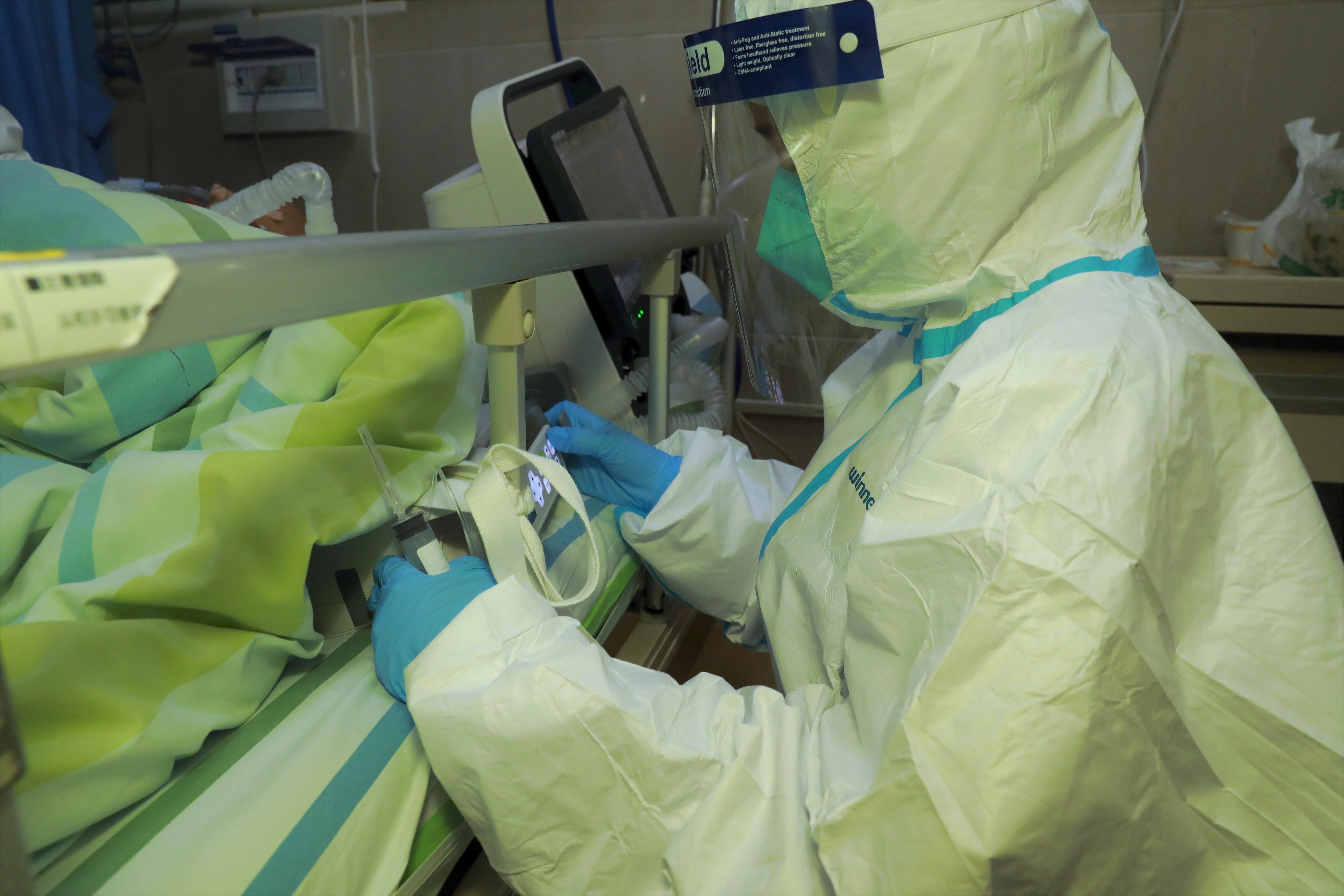 Un personal médico atiende a un paciente con neumonía causada por el nuevo coronavirus en el Hospital Zhongnan de la Universidad de Wuhan, 22 de enero de 2020. (cnsphoto vía REUTERS)