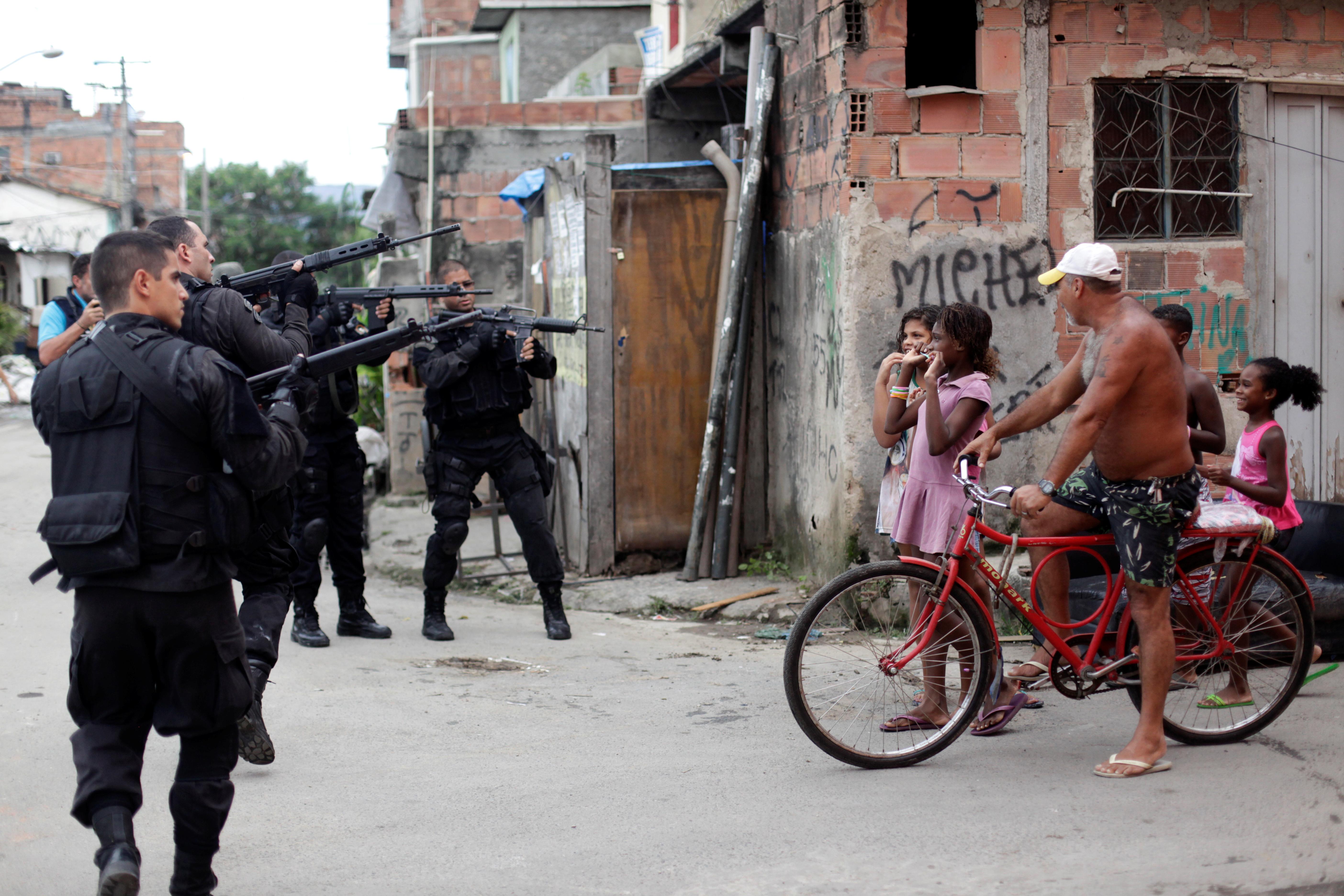 Vecinos se encuentran con un grupo de policías que toma posición durante una operación en el complejo de favelas de Mare en Río de Janeiro, Brasil, el 26 de marzo de 2014 (REUTERS/Ricardo Moraes/File Photo)
