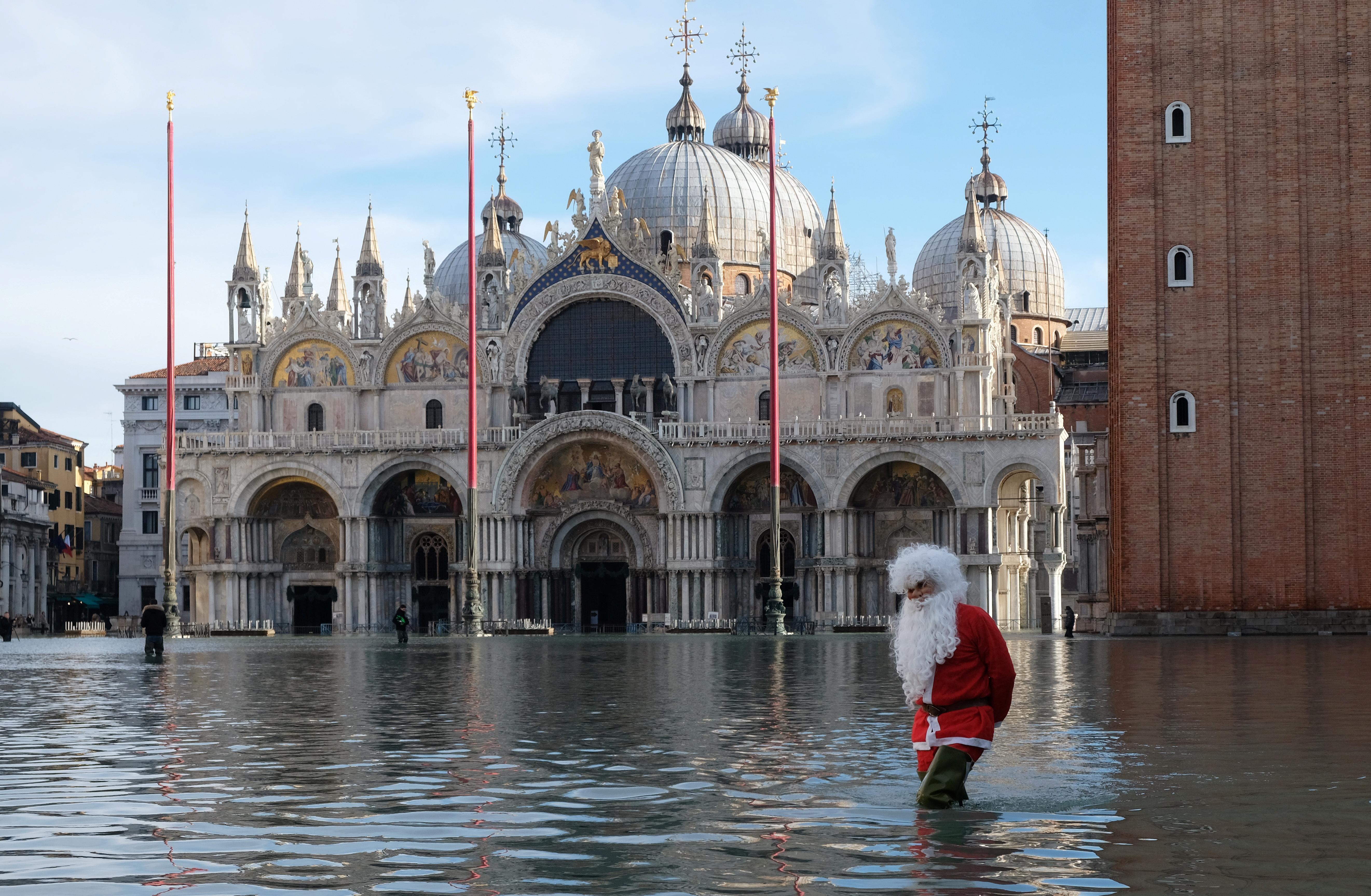 Un hombre vestido de Santa Claus vadeando las aguas de la inundación en la Plaza de San Marcos durante la marea alta en Venecia, Italia, el 23 de diciembre de 2019 (REUTERS/Manuel Silvestri)