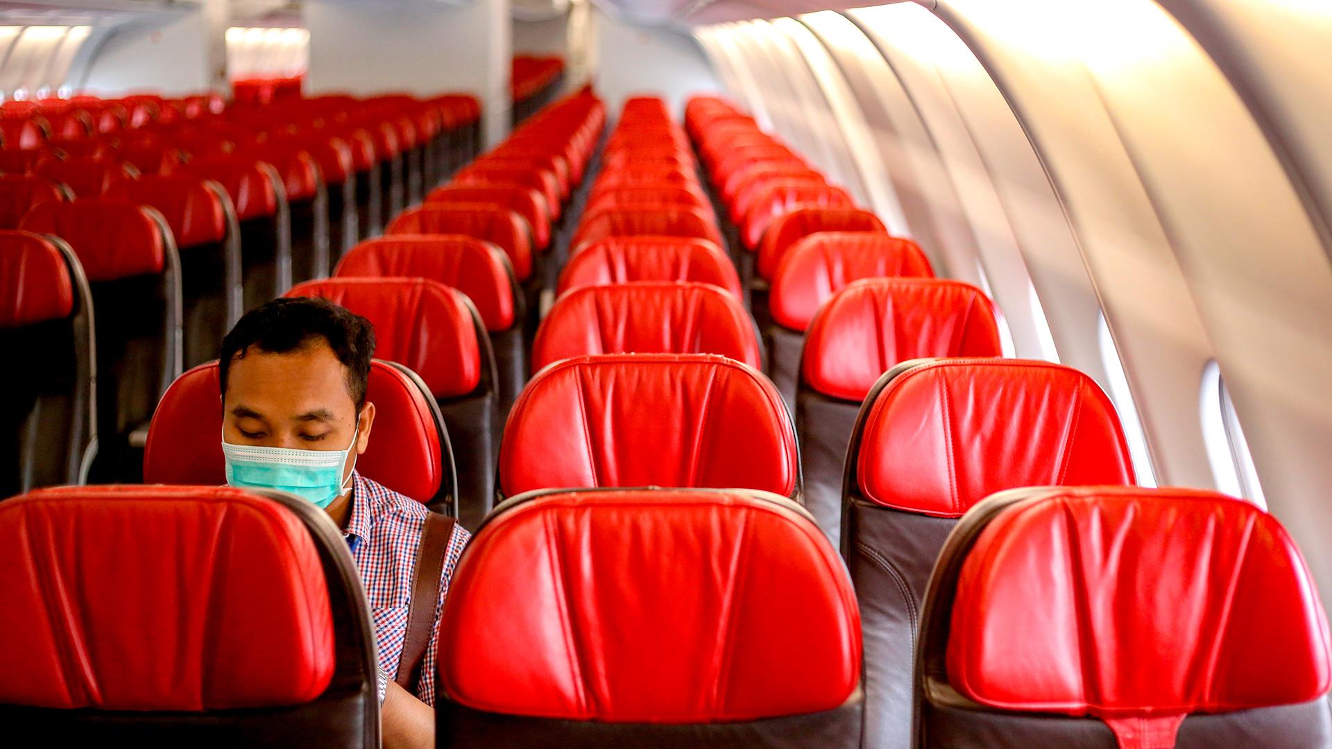 Un funcionario se sienta solo dentro de un avión antes de salir del aeropuerto de Yakarta en Tangerang el 1 de febrero de 2020, para llevar a los indonesios de regreso a casa desde Wuhan, China (ADAM TANJUNG / AFP)