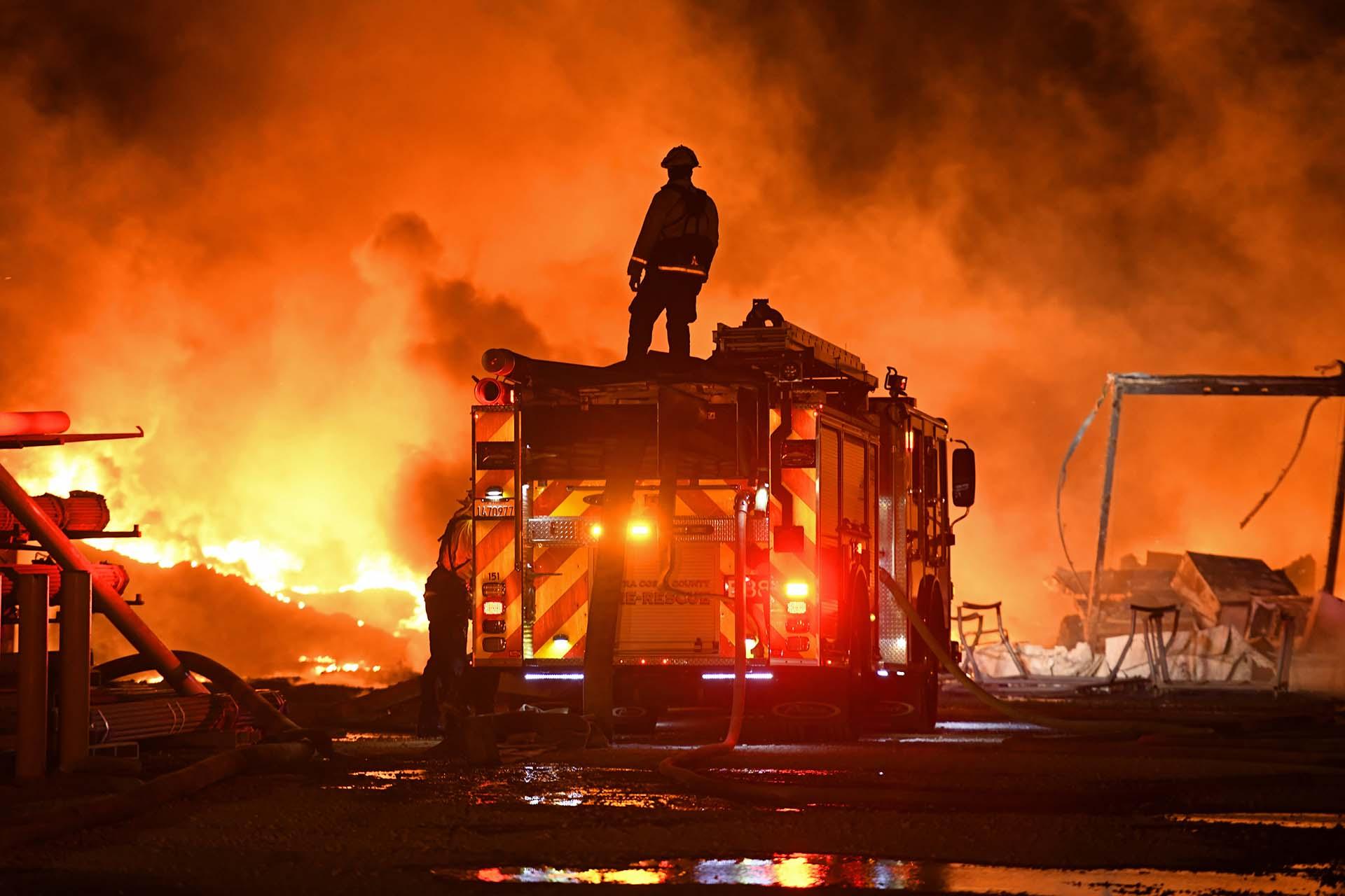 Un bombero se detiene para mirar un muro de fuego mientras lucha contra un incendio de hierba en East Cypress Road en Knightsen, California, el domingo 27 de octubre de 2019